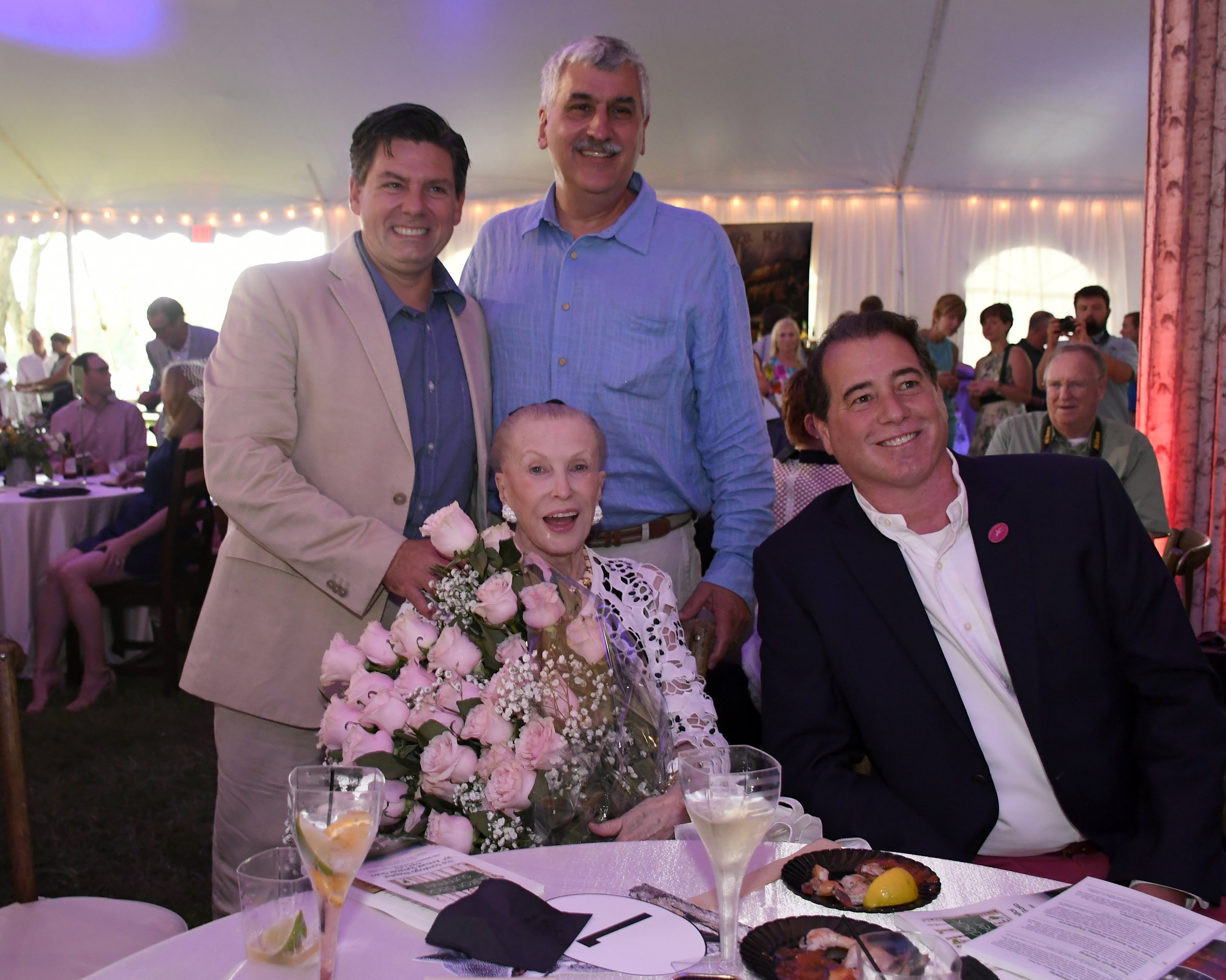 Marylou Whitney being presented with 35 pink roses in recognition of Marylou and John Hendrickson's tremendous support of Saratoga Hospital