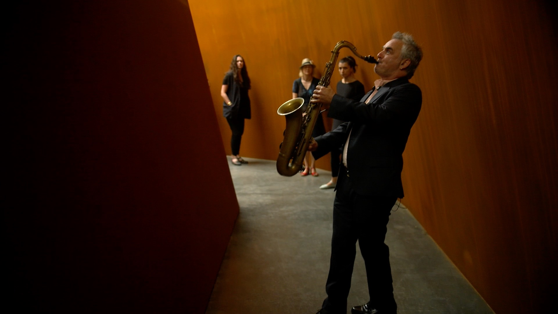 Audience members accompany Fefer as he interacts with Serra's monumental work.