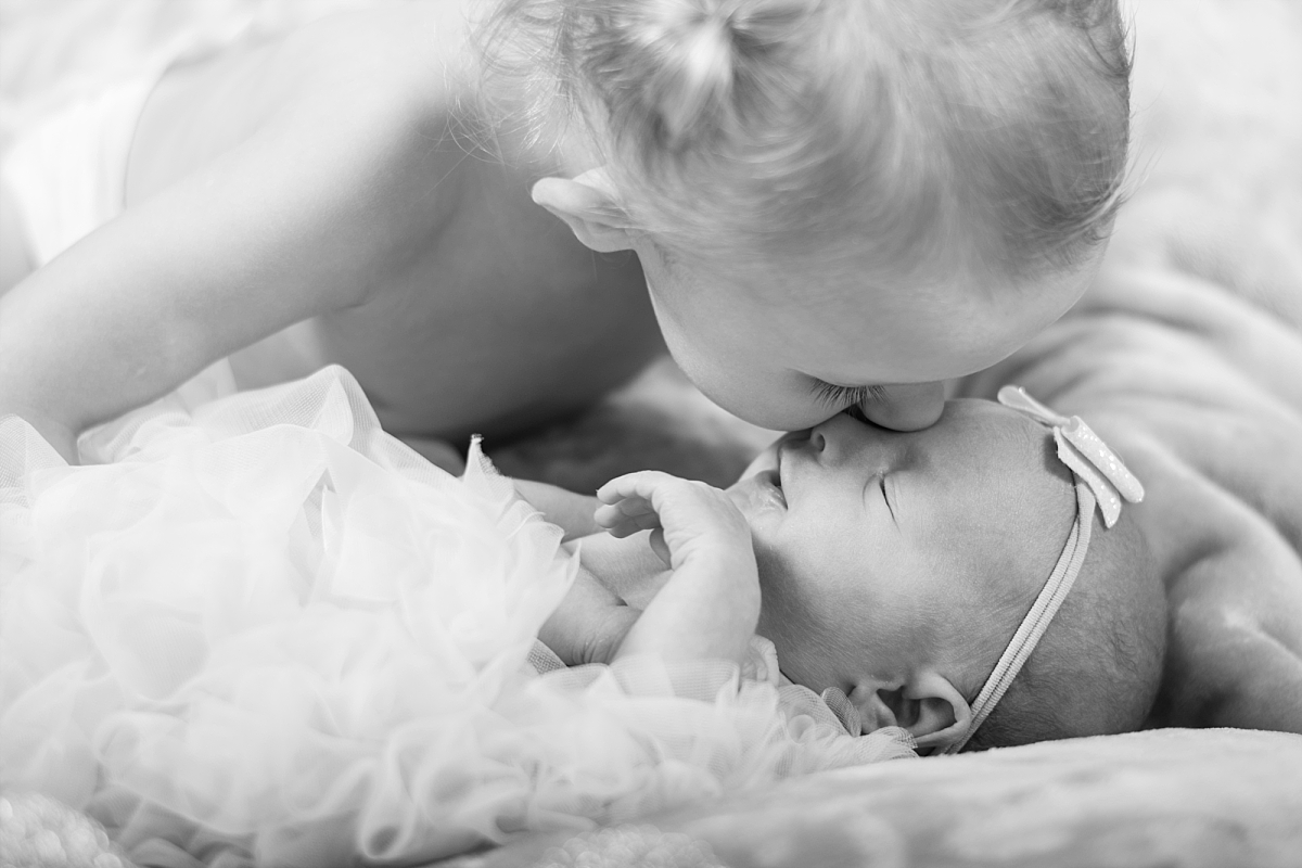 This shot just warms my heart so much! Big sister kissing her new little sis!
