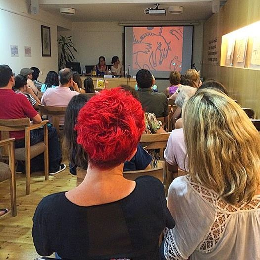 Presentation of Wonder Ponder at Ilustratour, Valladolid. July 2014. The image on the screen at the back shows a lion holding a goat in its jaw while its cubs await hungrily. Are animals cruel?