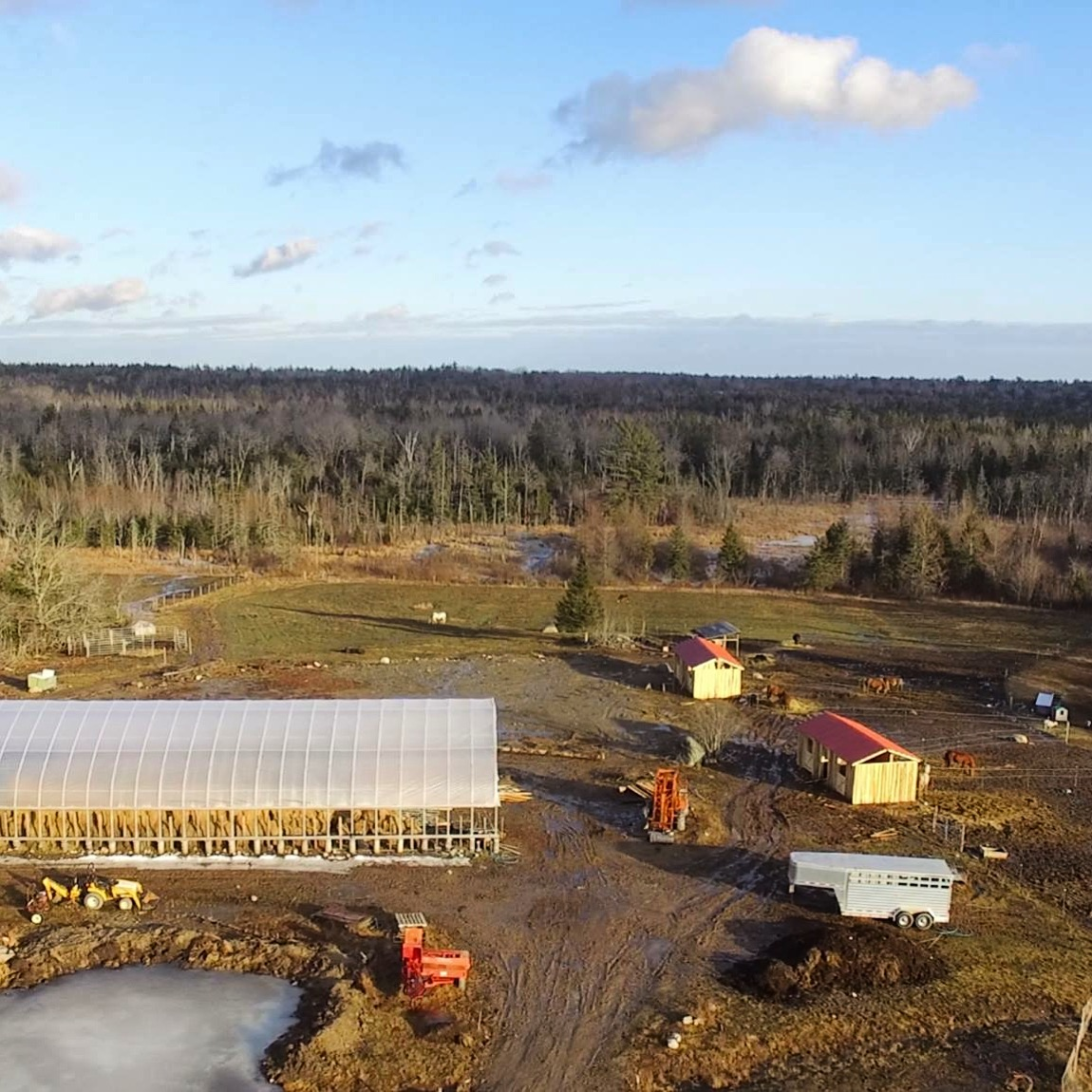 Bird's Eye View   The two red roofed buildings are the horse sheds. The large hoop structure is our hay storage/riding ring combo. And yeah, that pond is solid ice still, despite the melting mud in the road…