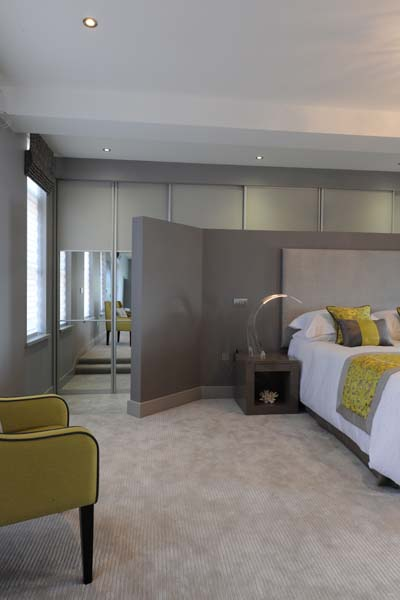 Built in wardrobes to the rear of the bedroom zone protect the historic tiling in this unit.
