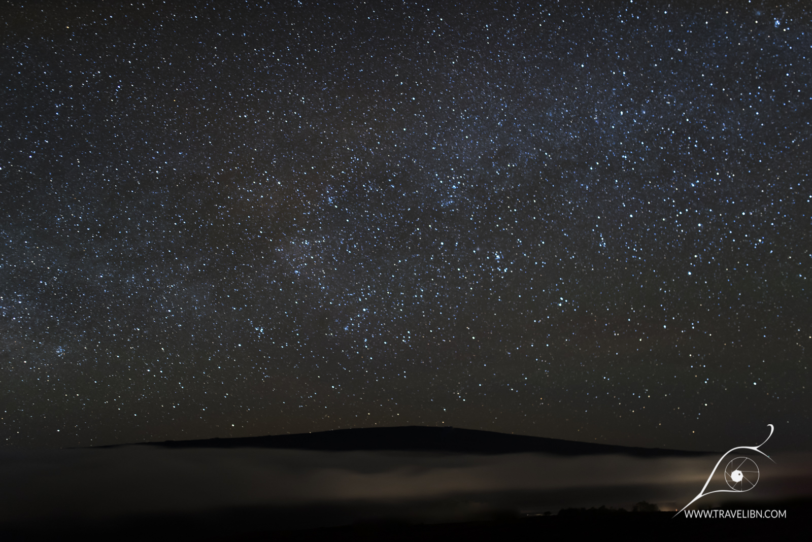 Mauna Loa, the world's largest shield volcano and the heaviest mountain on Earth, dwarfed by the night skies. As seen from atop Mauna Kea