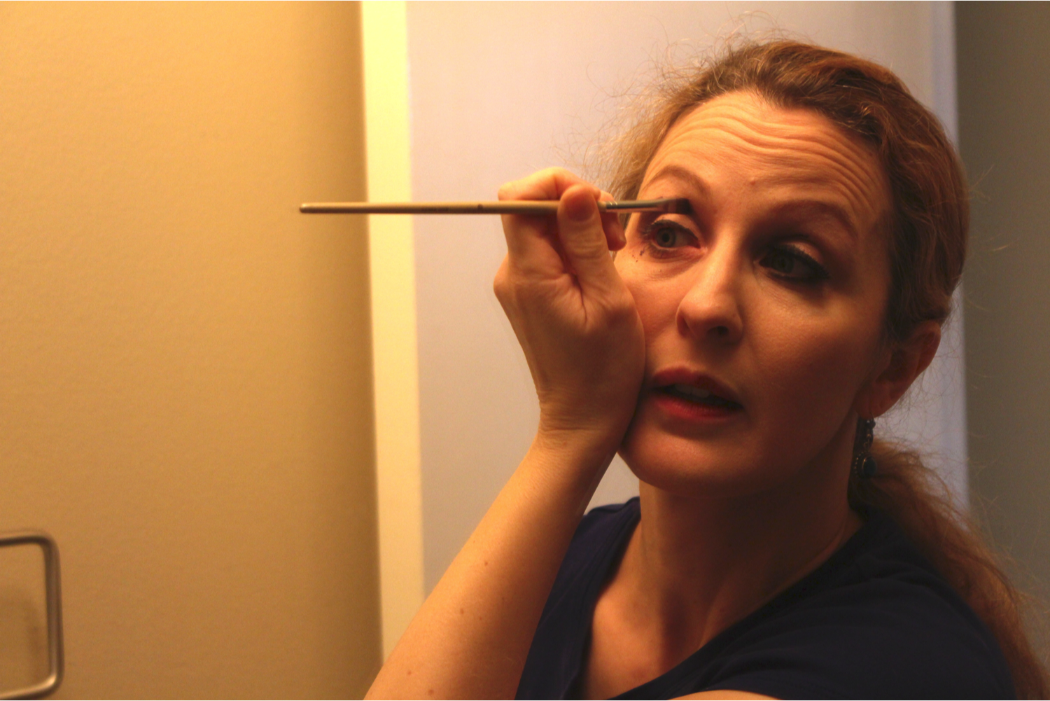Amara applies eye shadow in her personal studio's bathroom.