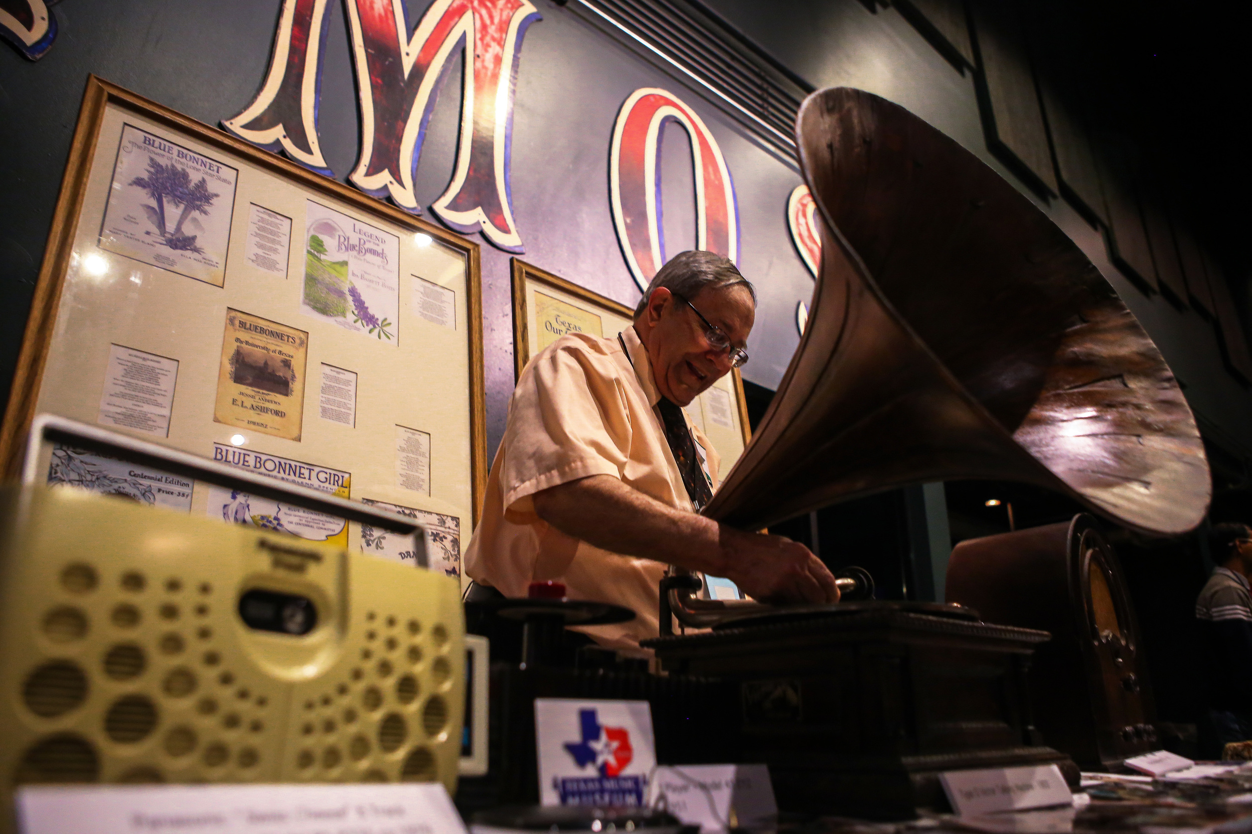 "The Texas Music Museum display various pieces of their collections from left to right: a Panasonic ""Swiss Cheese"" 8 Track Stereo Player, a Type D Victor Talking Machine and an antique radio."