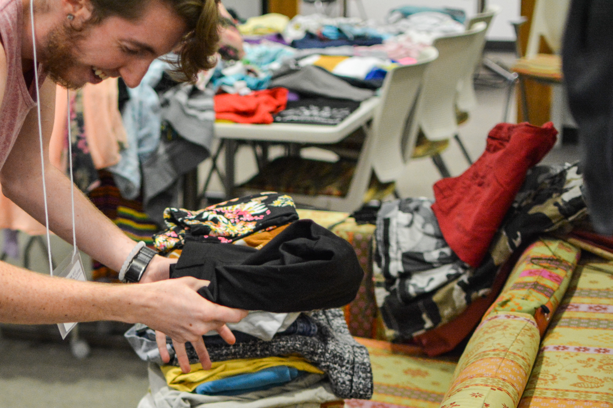 A student worker is all smiles at the Gender and Sexuality Center as he helps put leftover clothes into piles.