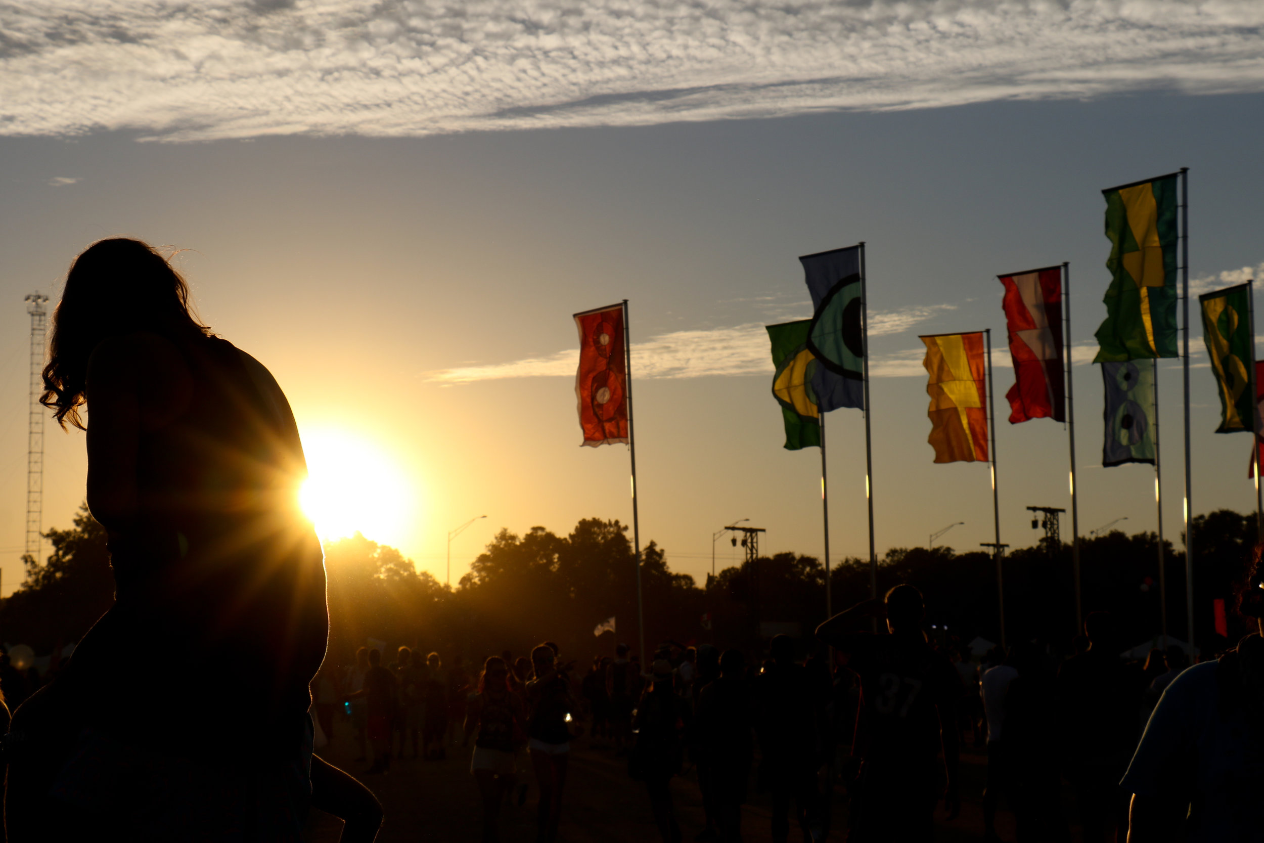 A festival-goer overlooks the festival from her friend's shoulders.
