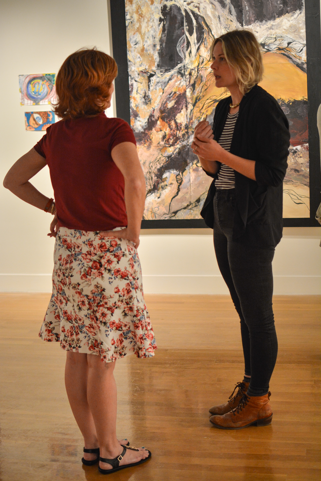 Two people who attended the Study Abroad Art Show in the Visual Art Center discuss the pieces on display.