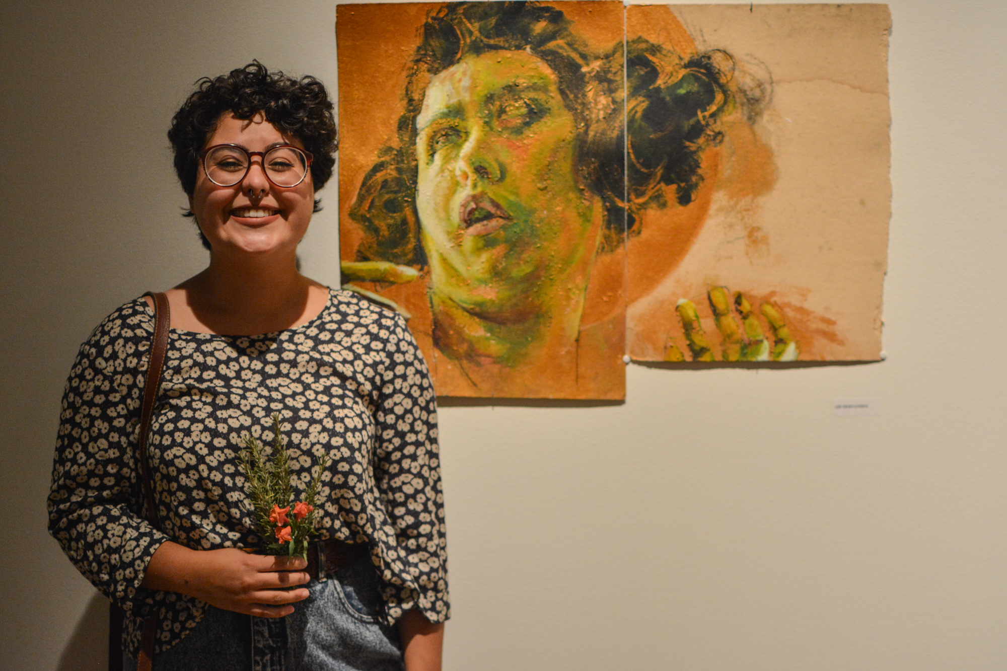Abi Hernandez smiles widely near her piece at the Study Abroad Art Show in the Visual Art Center. Her art piece is made on cardboard she found lying around in Italy.