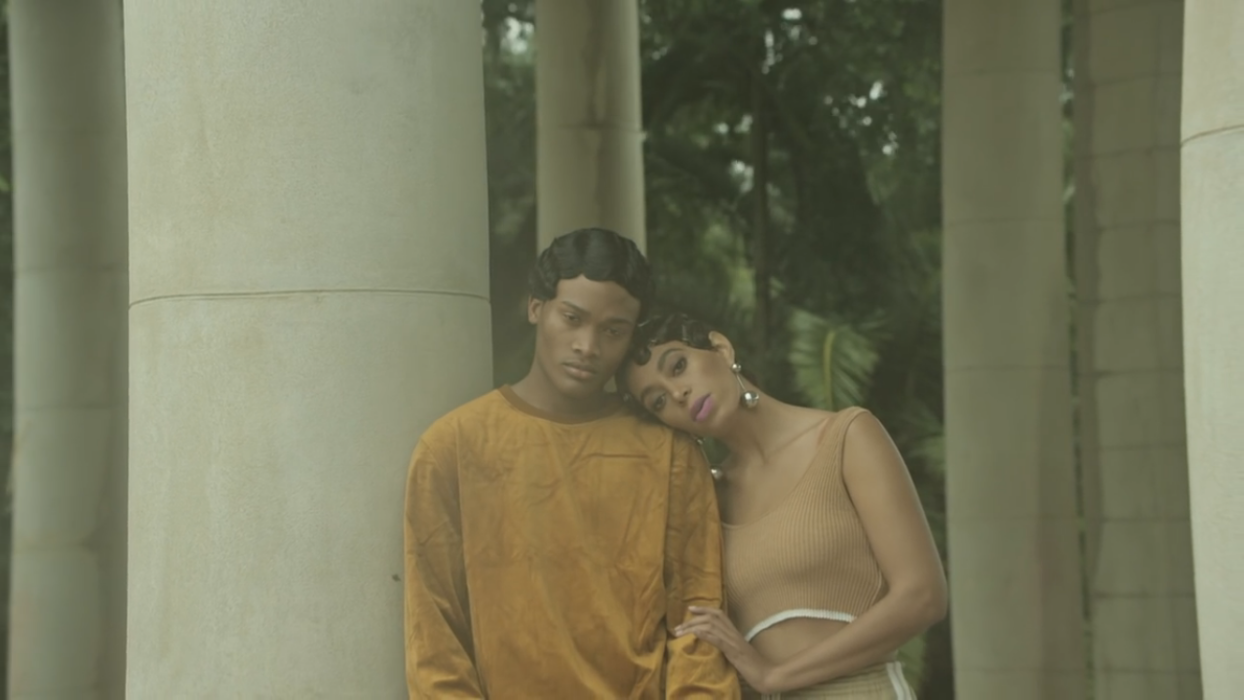 Solange wearing a nude cropped tank top with large silver earrings, light makeup and 1920s inspired hair.