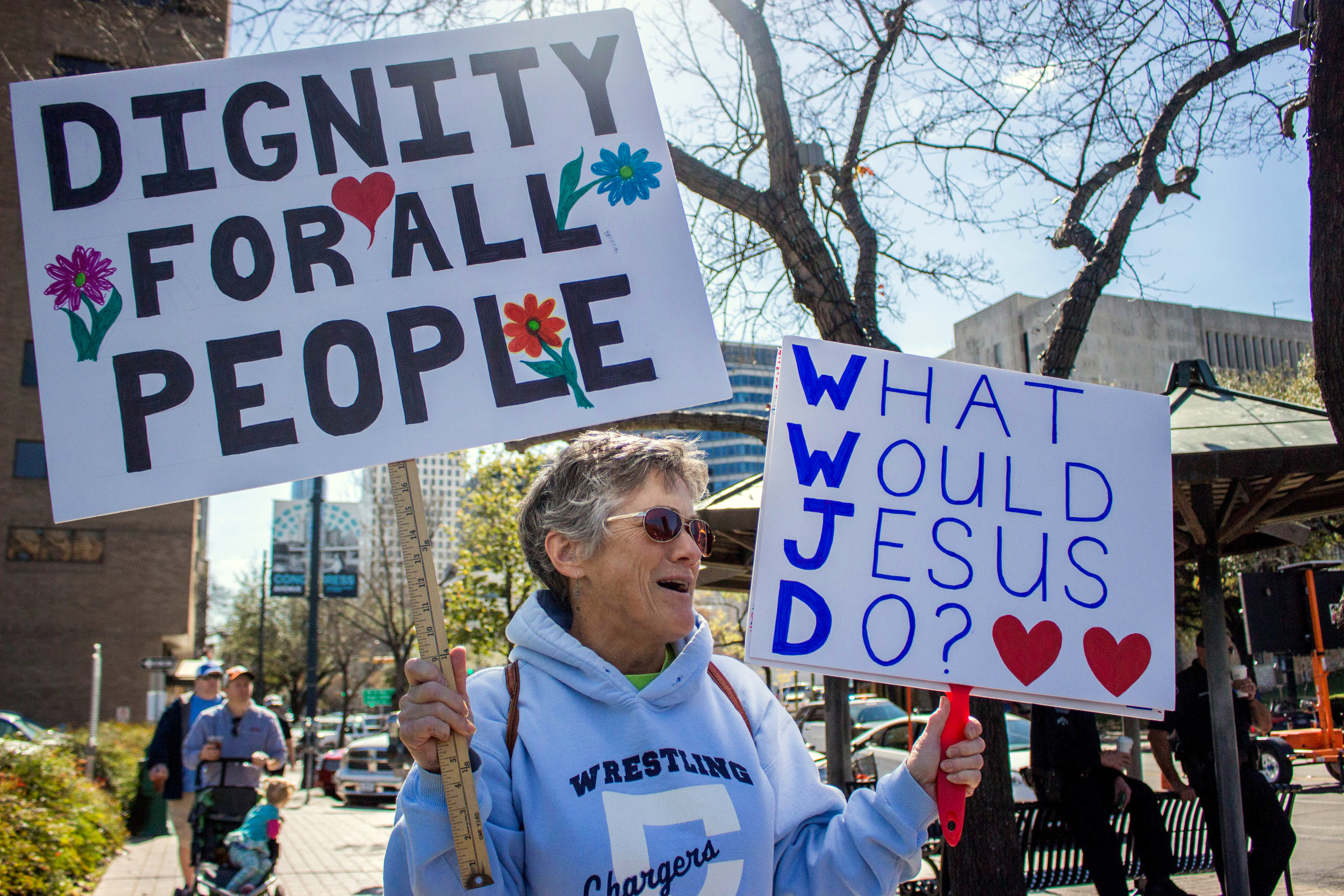 """Claire Kennedy holds two signs at the """"No Ban, No Wall"""" protest. One reads, """"Dignity for all people"""" and the other says, """"What Would Jesus Do?"""""""