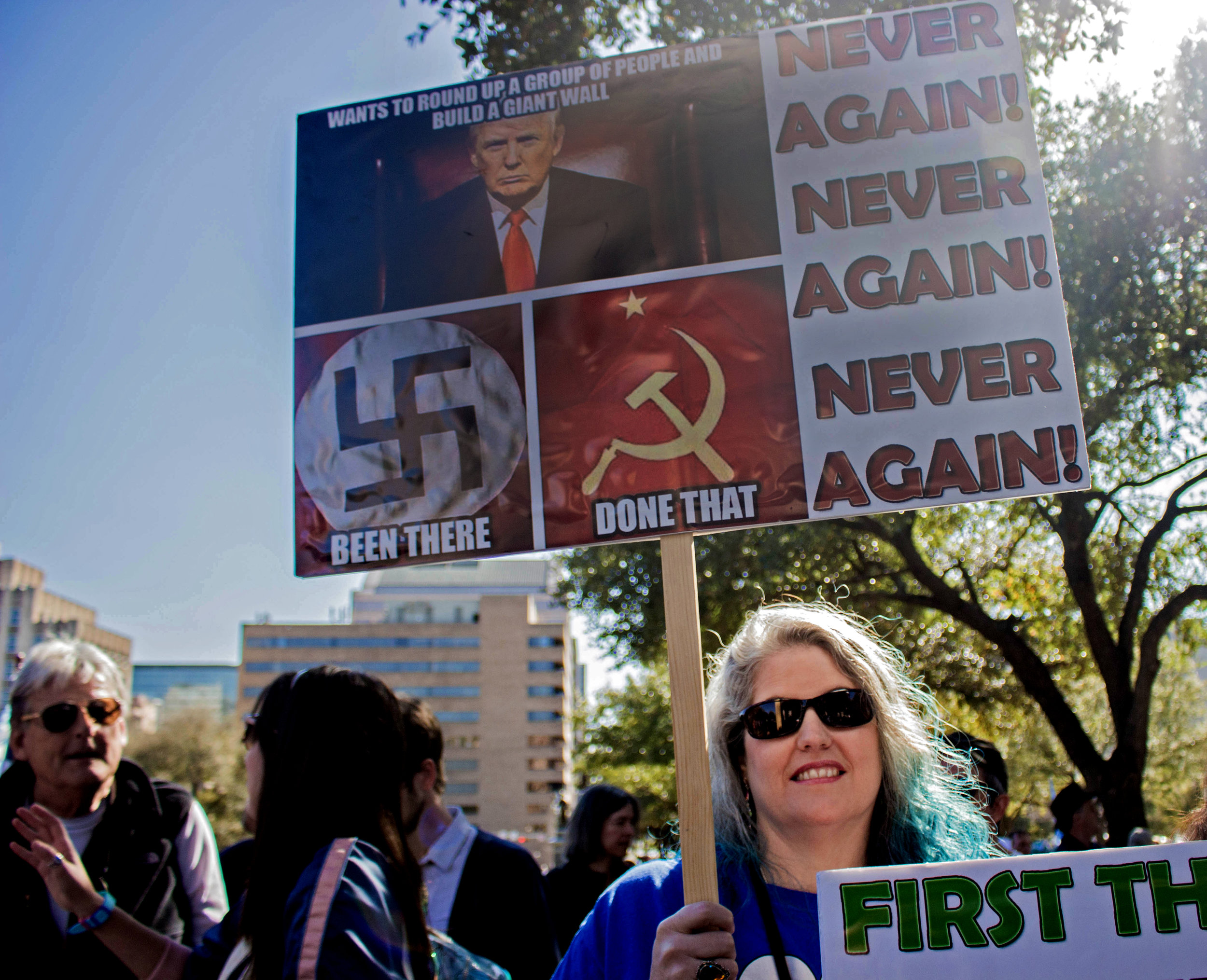"""Tanya Welch holds a sign that says, """"Never Again! Never Again! Never Again!"""" at the rally."""
