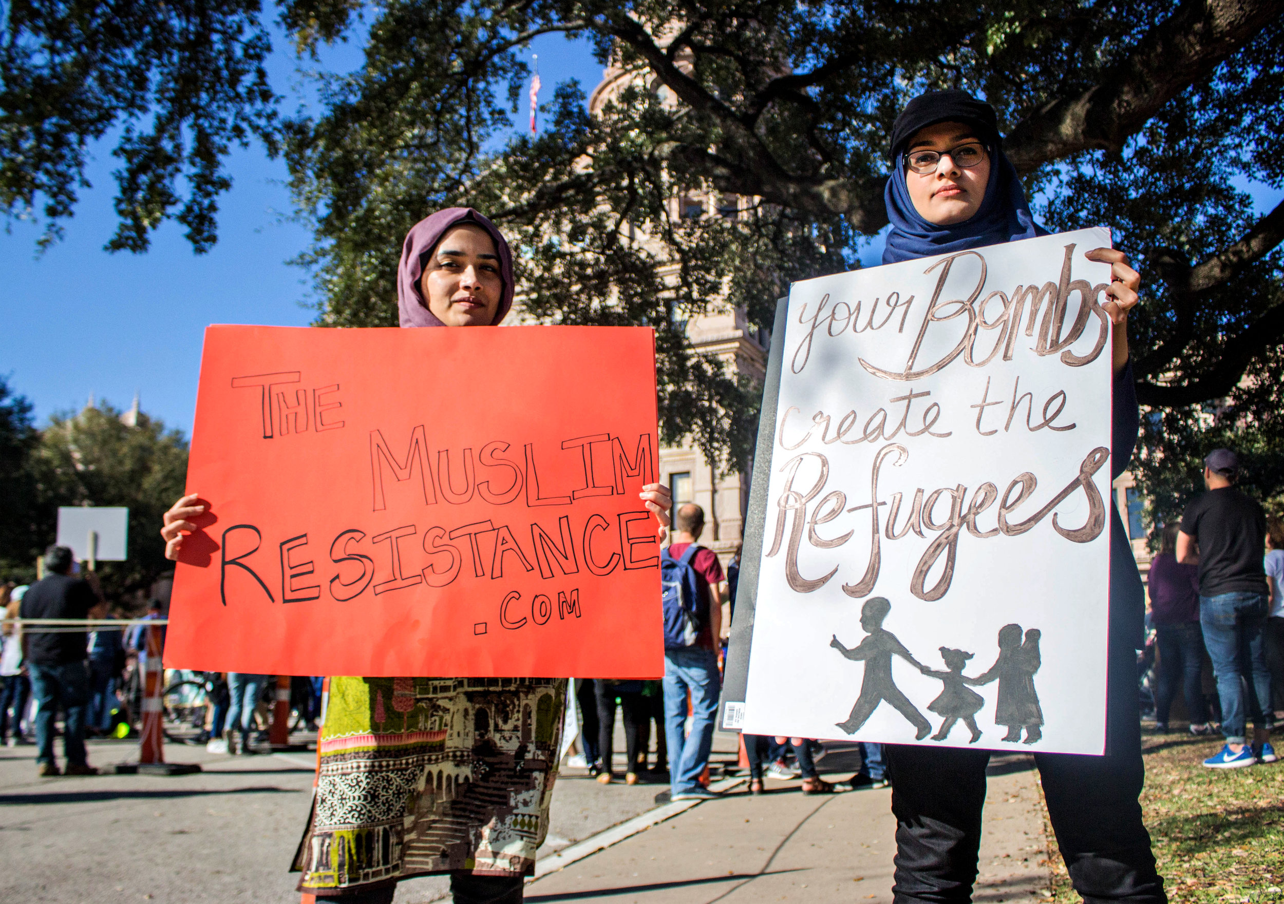 """Zainab Haider, right, holds a sign that says, """"Your bombs create the refugees"""" and Tasbiha Batool, left, holds a sign that says, """"The Muslim Resistance .com"""" near the Capitol."""