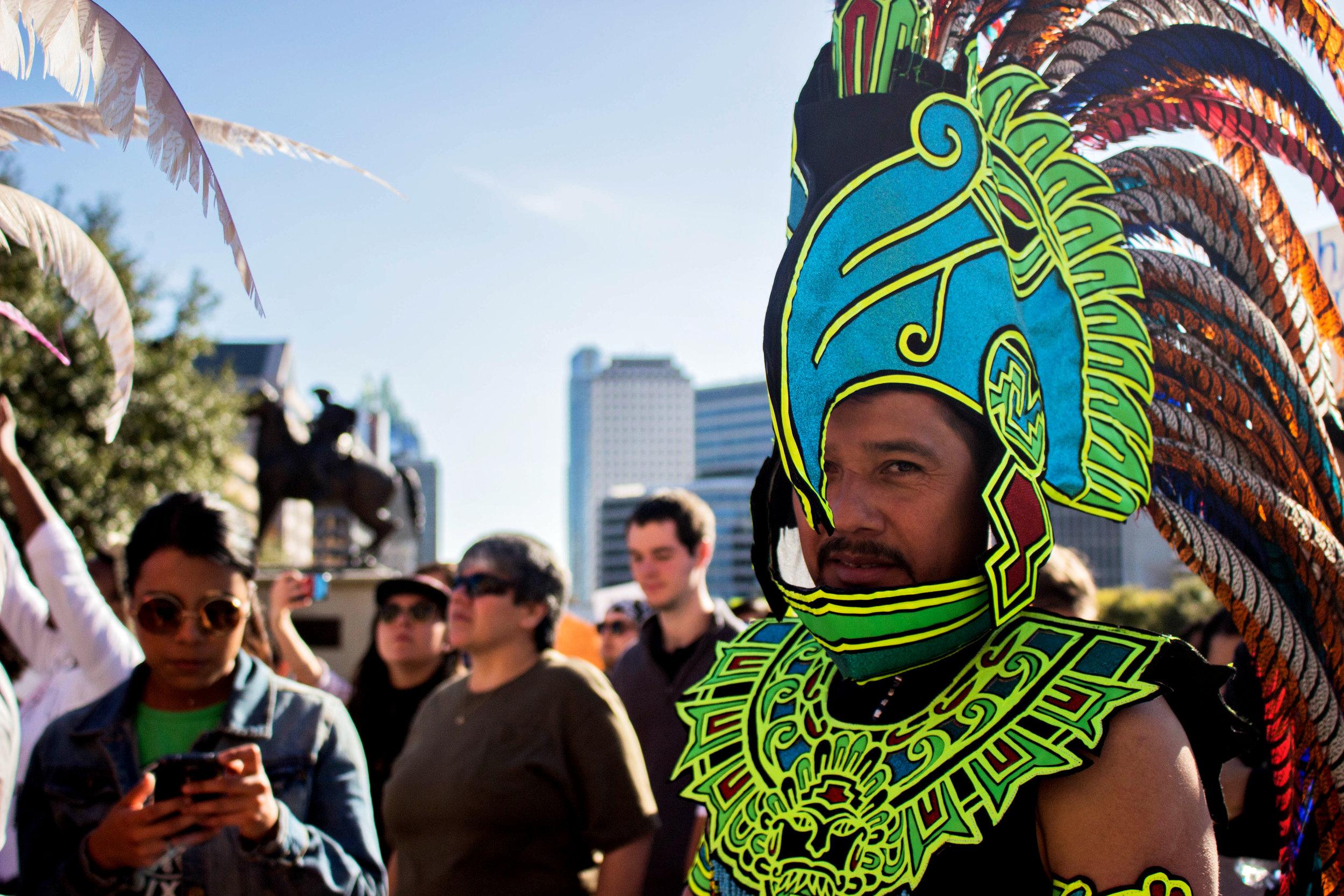 "Santos Diaz wears a green headdress at the ""No Ban, No Wall"" rally."