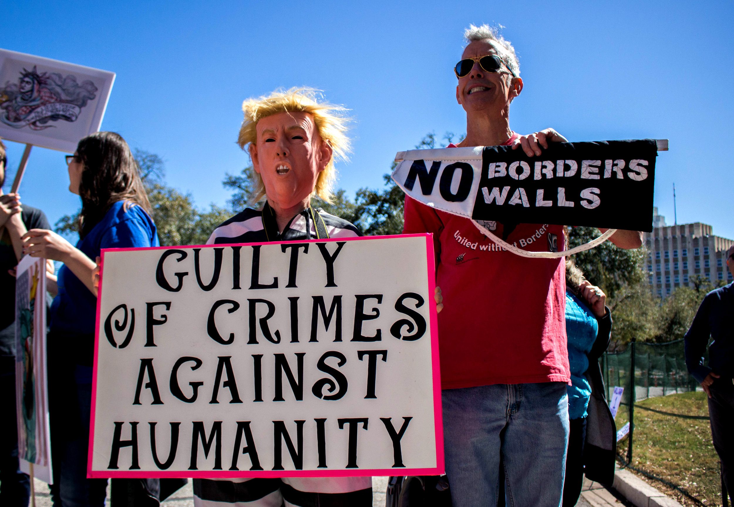"""Two protestors hold a signs that say, """"Guilty of crimes against humanity"""" and """"No borders/walls"""" at the rally. One protestor is wearing a Trump mask."""