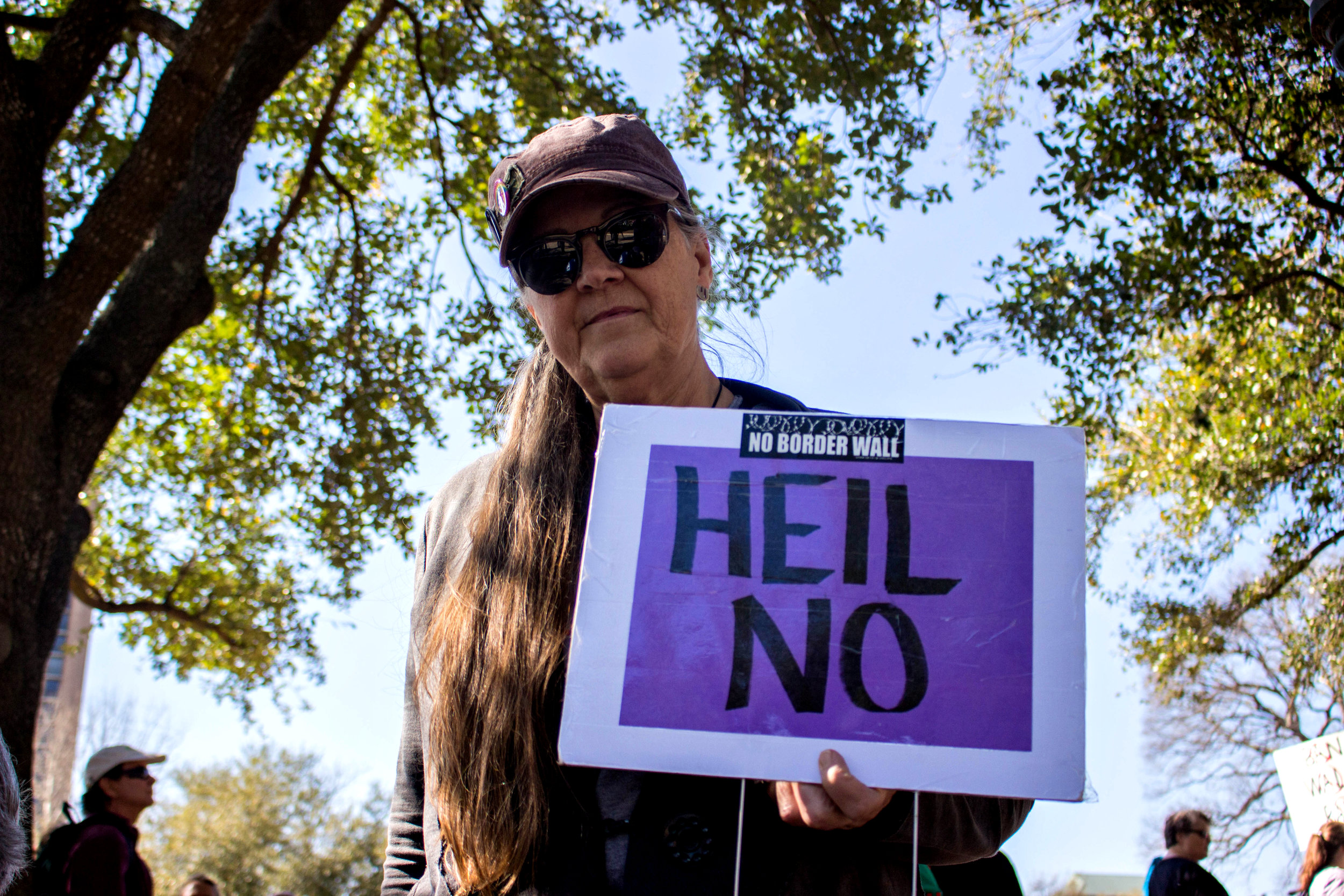 """A woman at the rally holds a sign that says, """"Heil no"""" at the """"No ban, no wall"""" rally on Saturday."""
