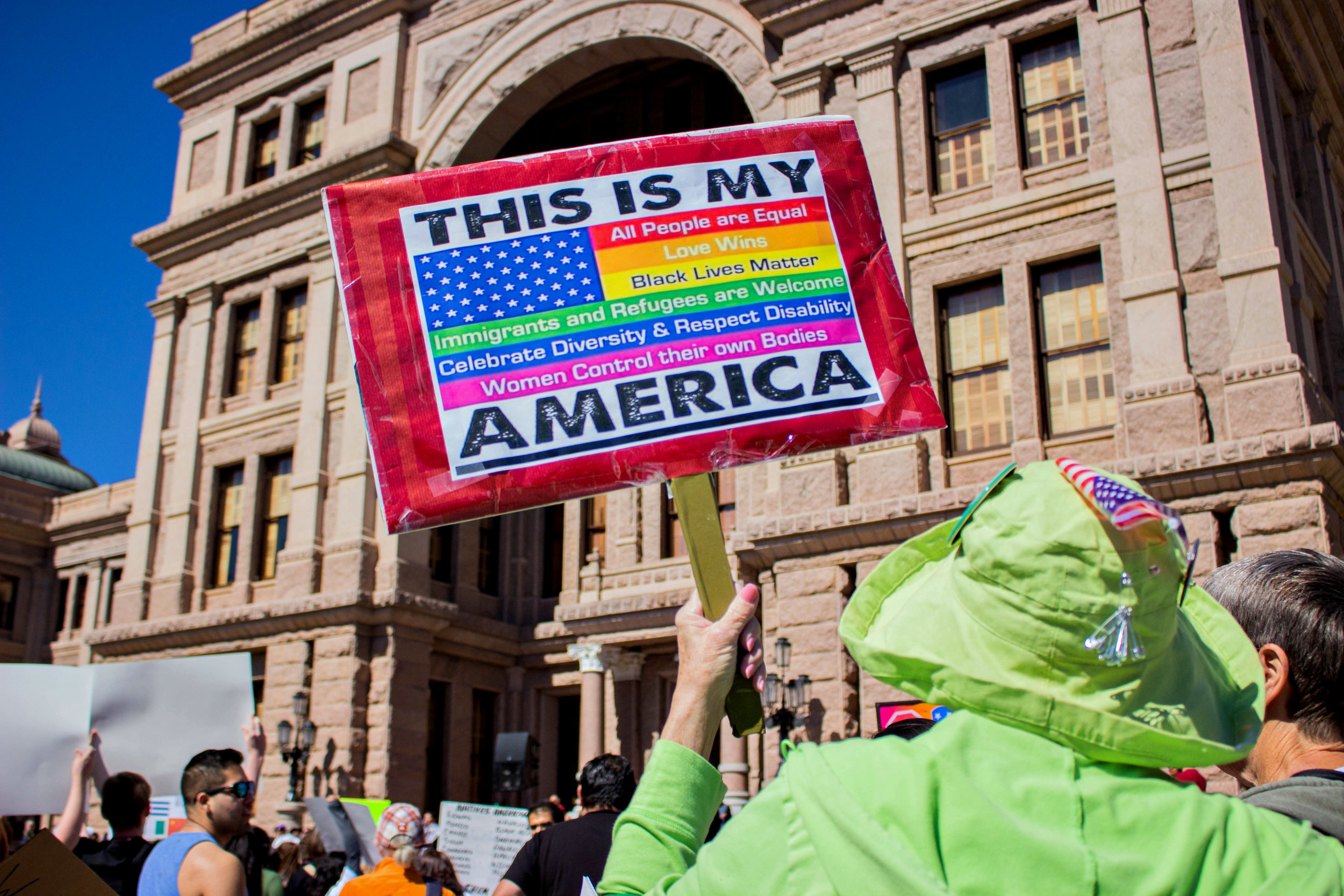 """A protestor holds a sign that says, """"This is my America"""" with a rainbow American flag."""