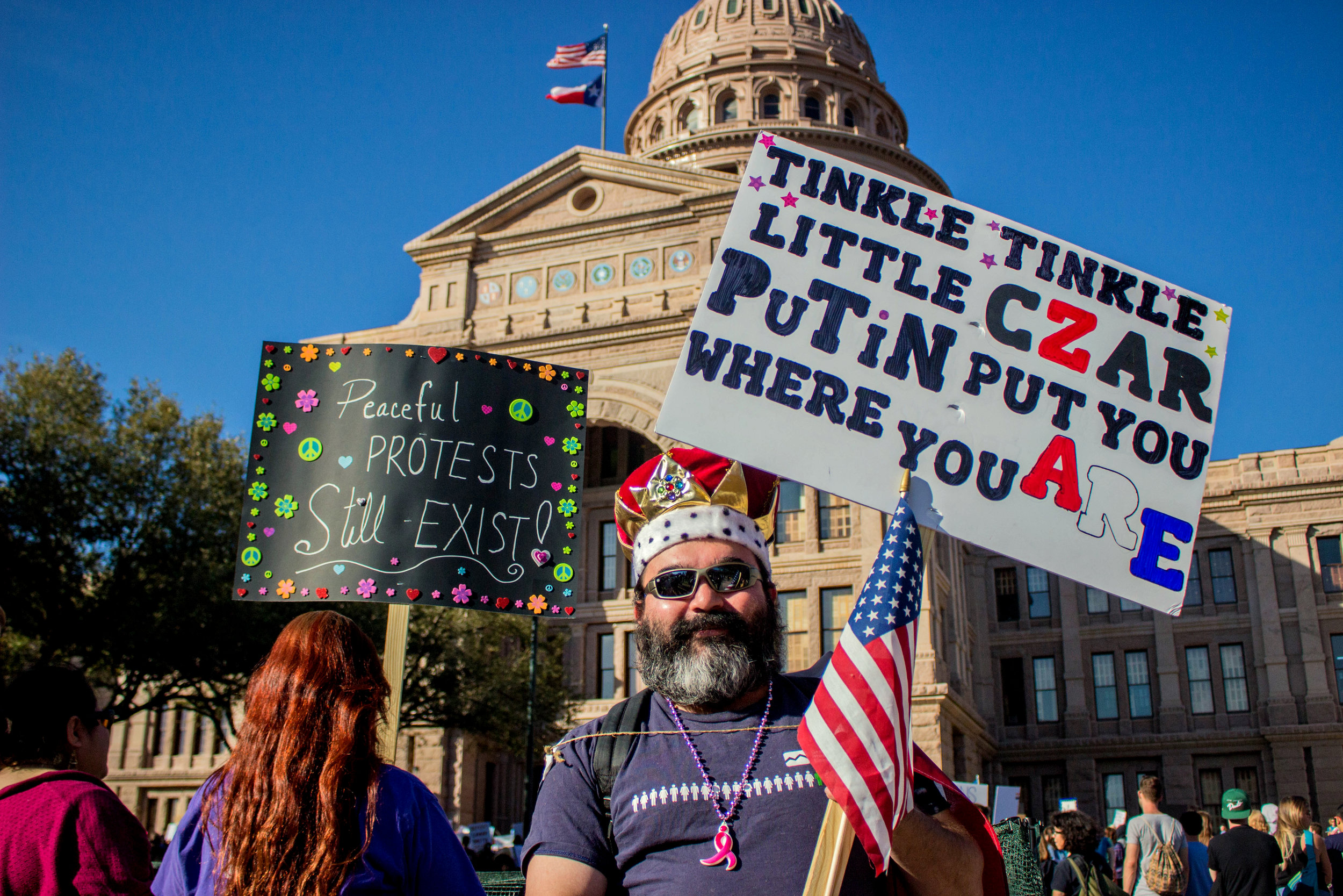 """A man wearing a crown holds a sign that says, """"Tinkle, tinkle little czar Putin put you where you are"""" in front of the Capitol."""