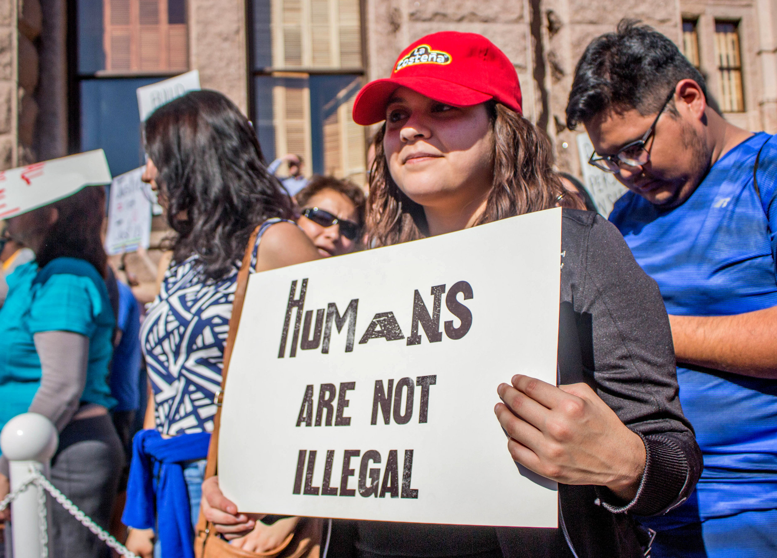 """Mariana Rodriguez holds a sign that says, """"Humans are not illegal"""" in front of the Capitol."""