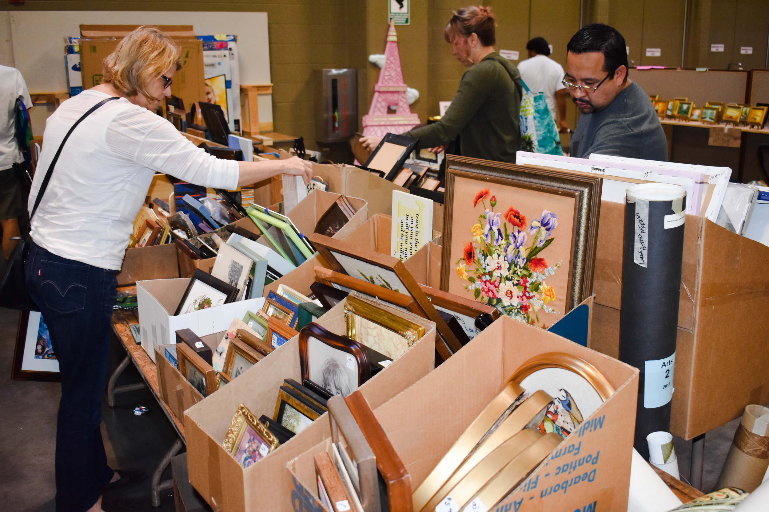 Sale attendees peruse through boxes of antique art collectibles.