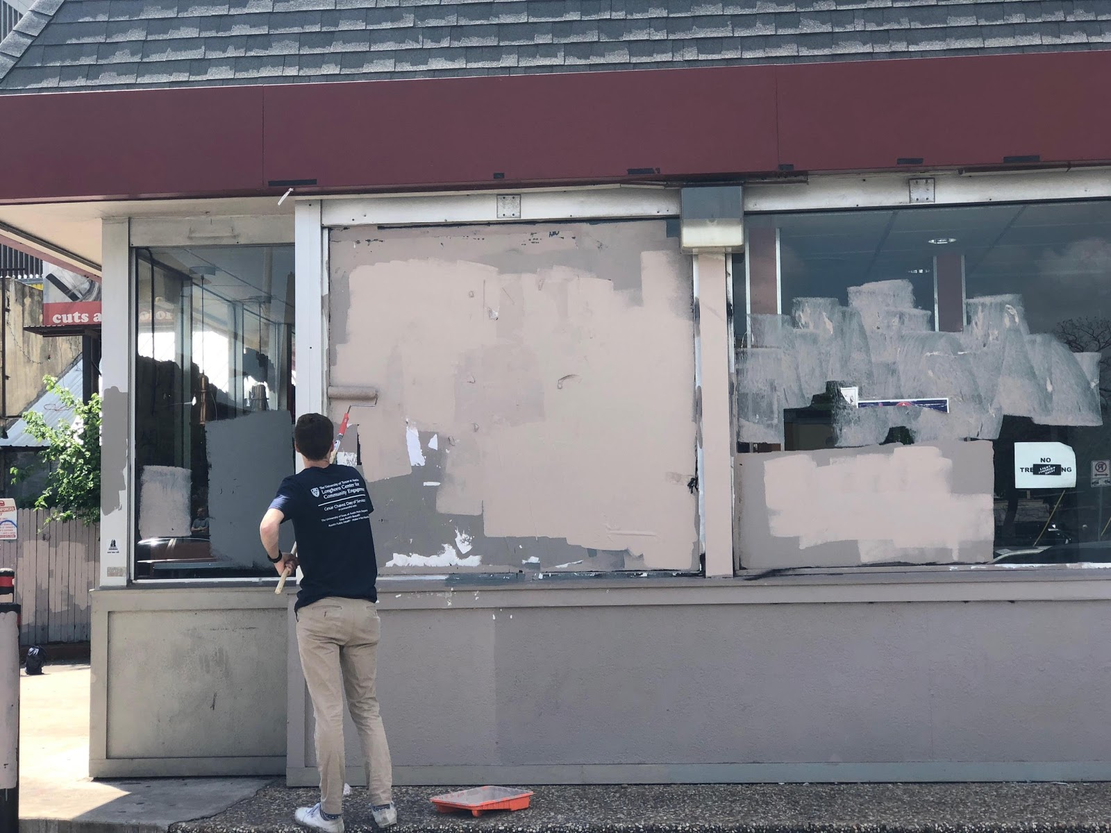 A volunteer paints over graffiti on a former Jack In The Box's window.