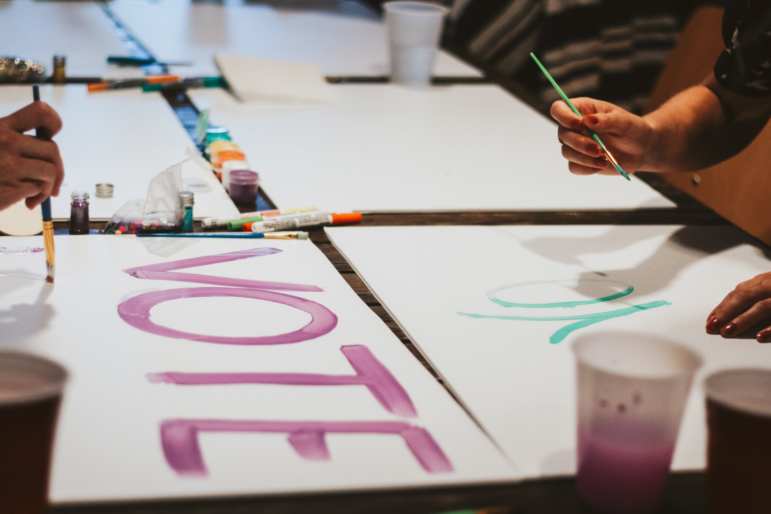"Participants paint posters with the word ""vote"" in an effort to promote its importance, especially in this upcoming election."