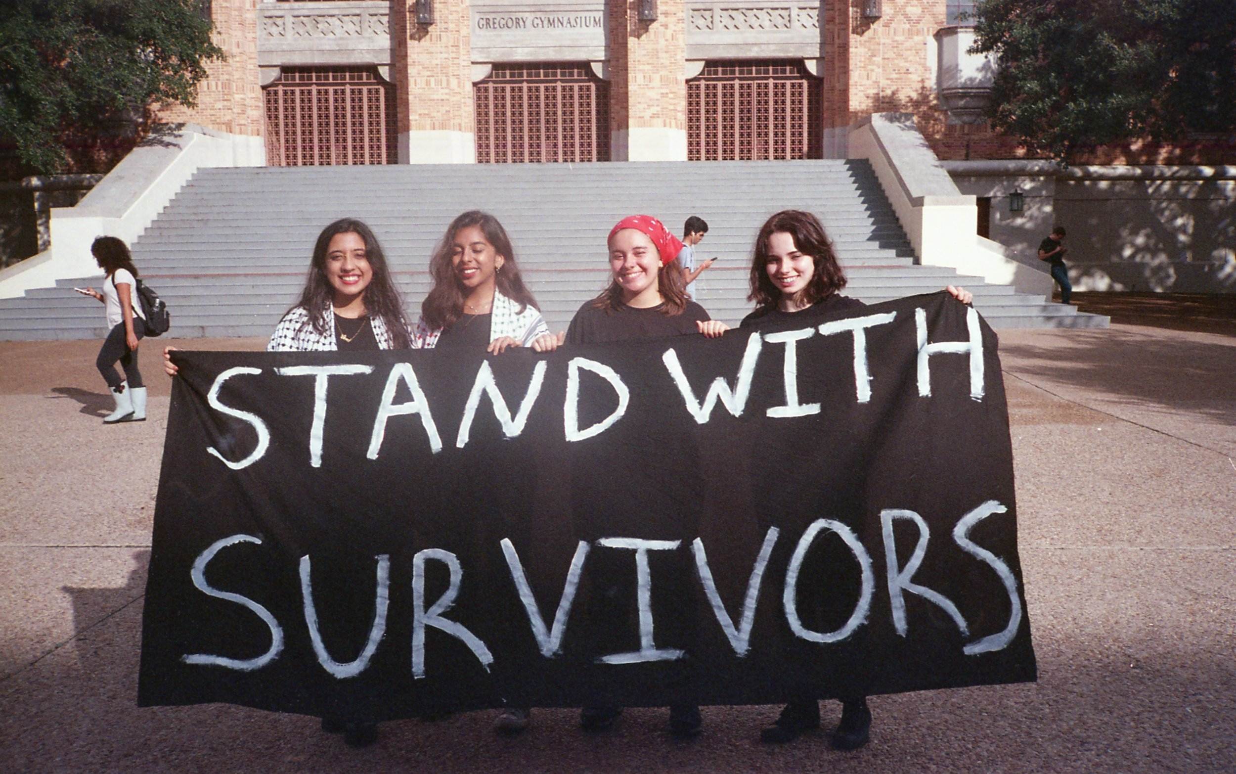The organizers of the event, Sonya, Rimsha, Angel and Sarah pose for a photo with a Stand with Survivors sign