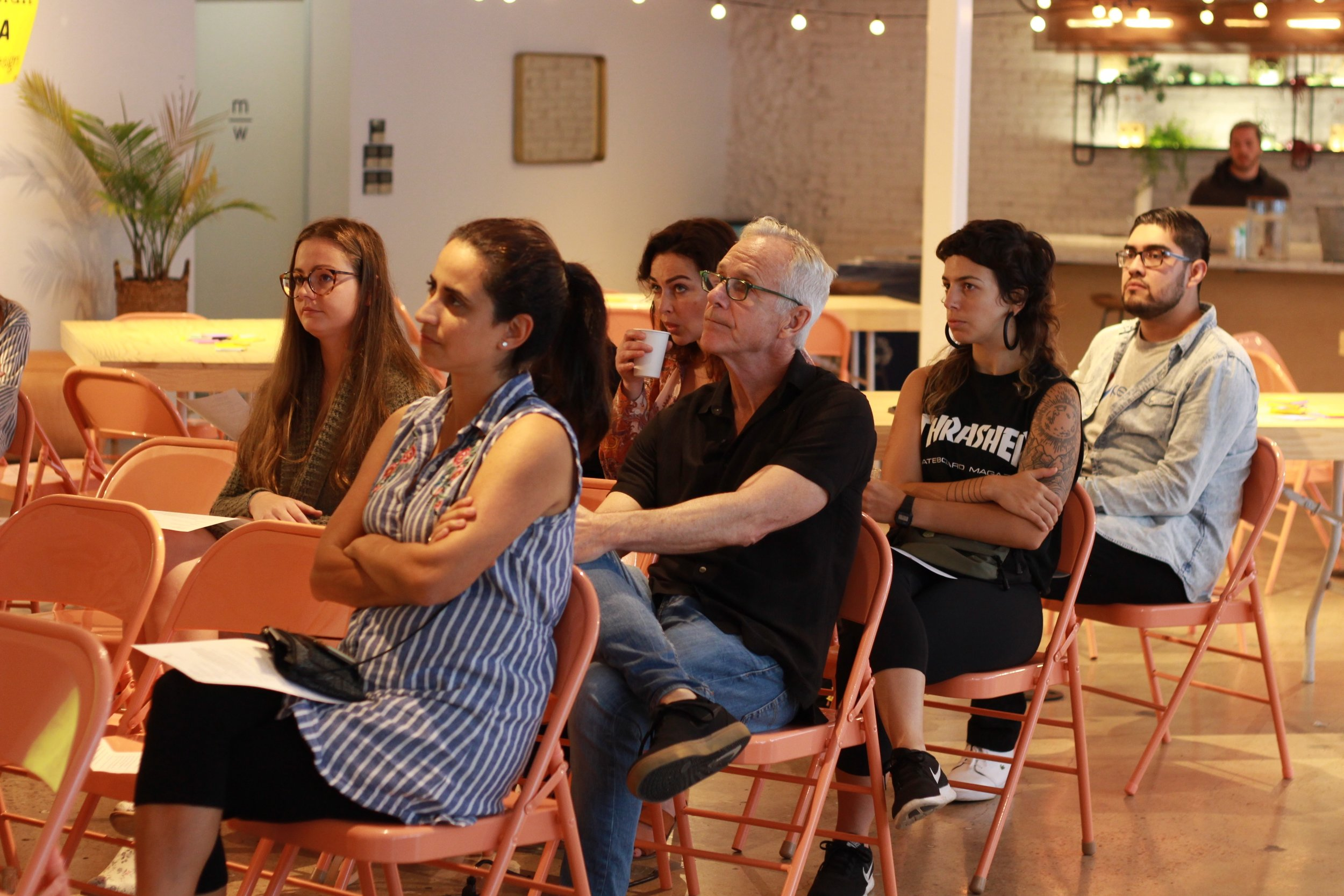 The crowd attentively listens and participates in the discussion.
