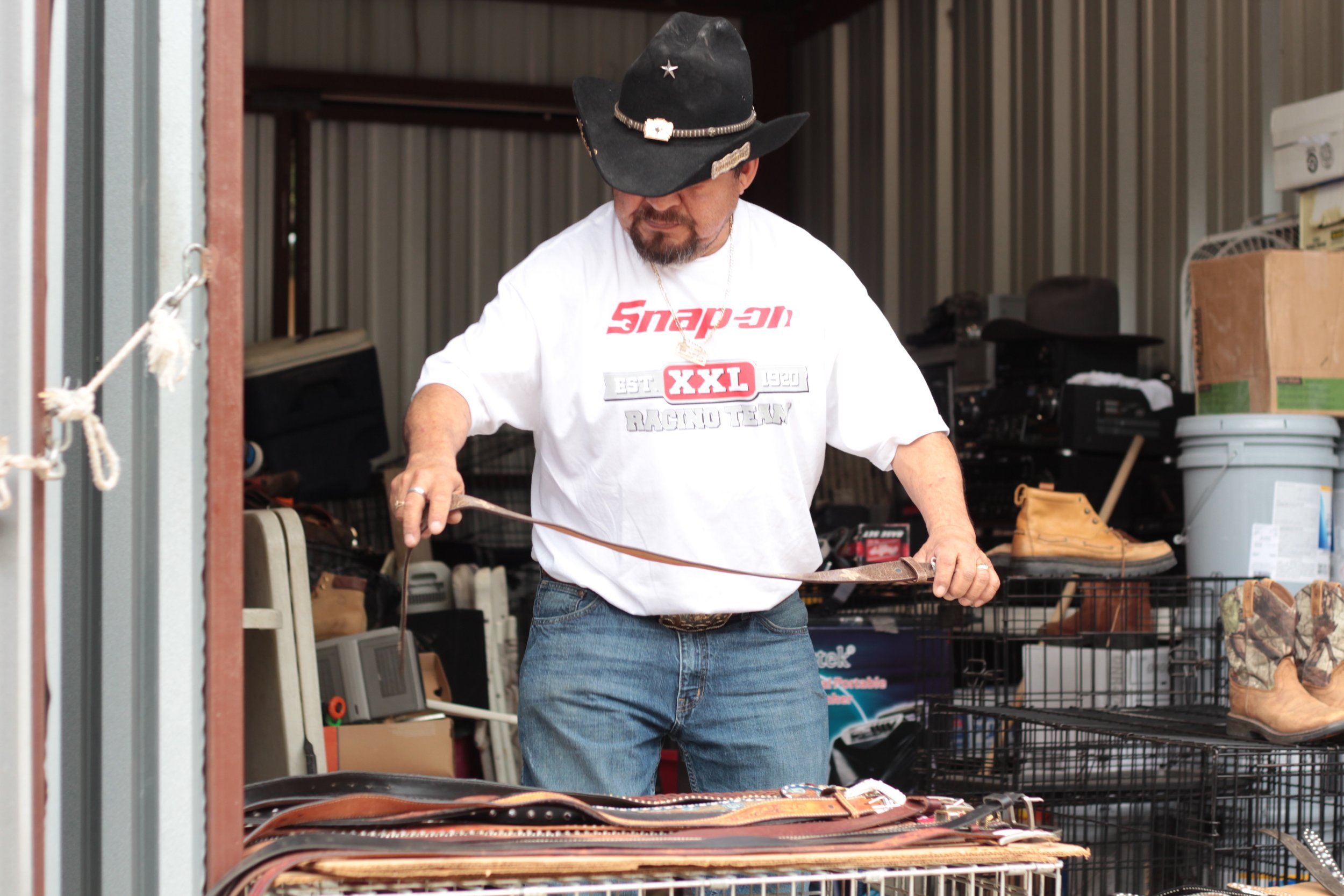 Vendor Ricardo lays out leather belts before he opens for business at the 812 Market.