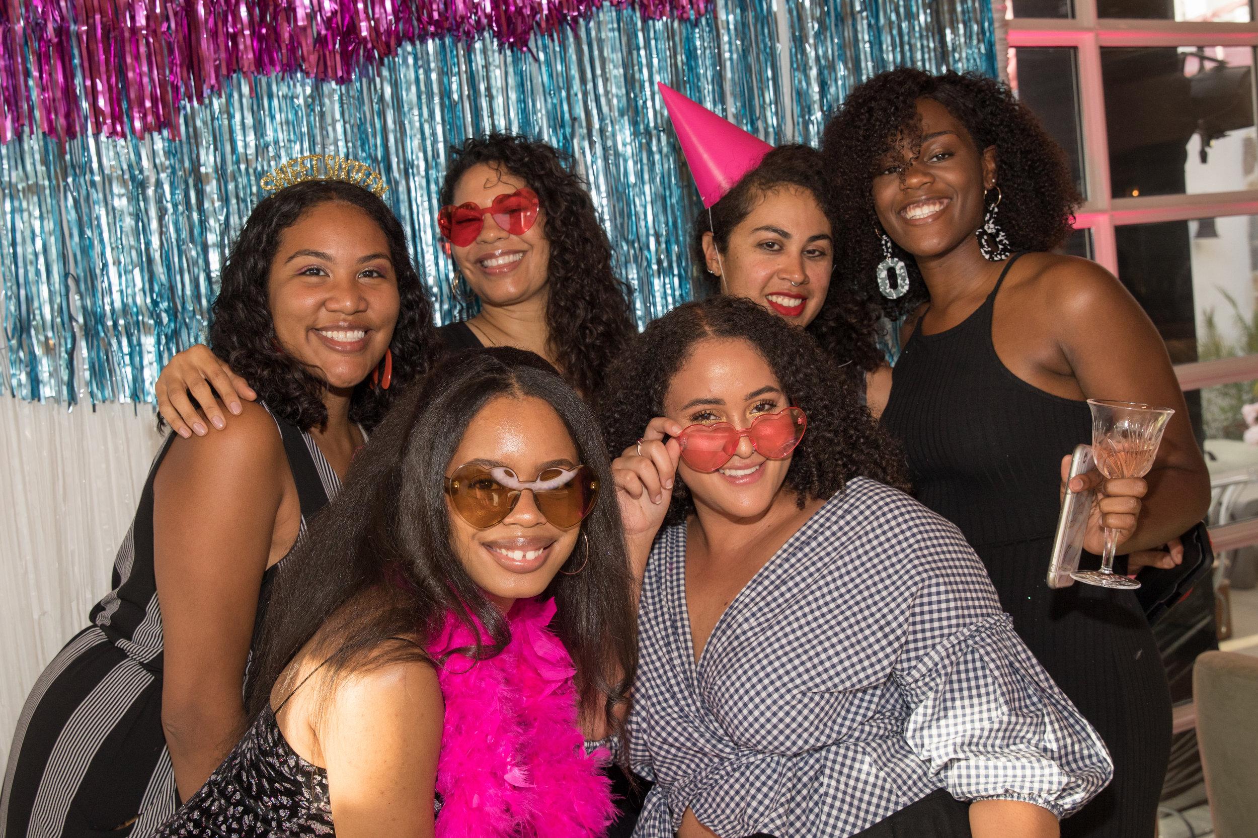 Party guests stack up on props and crouch behind the photo booth to get the perfect shot.