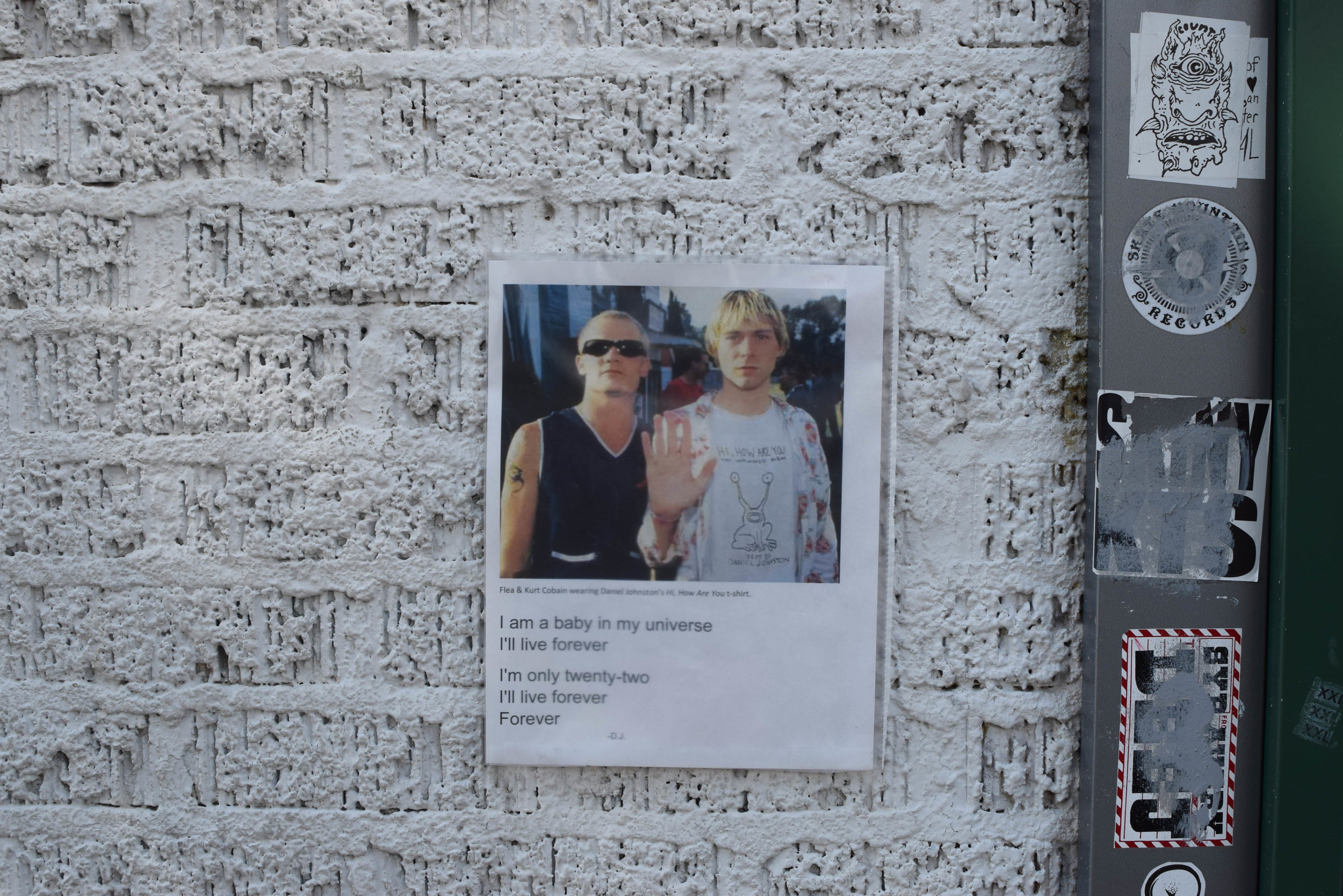 "A post with a photo of Flea and Kurt Cobain on the famous mural. Cobain wears a ""Hi, How Are You"" t-shirt."