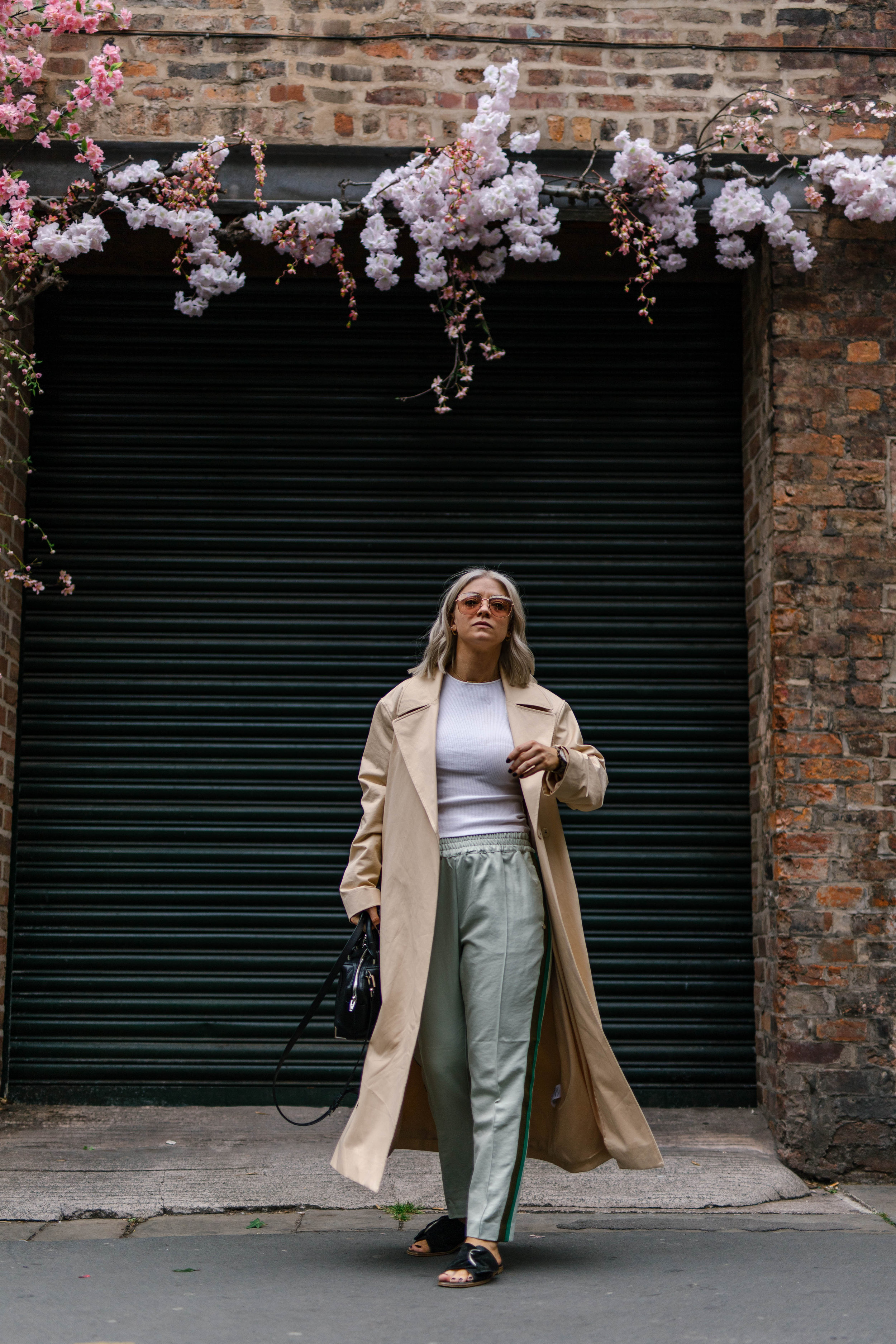 sporty spice outfit, with scotch and soda trousers, & other stories trench coat outside a florist in the northern quarter manchester, with blonde bob hair cut, joey taylor, northern magpie 5