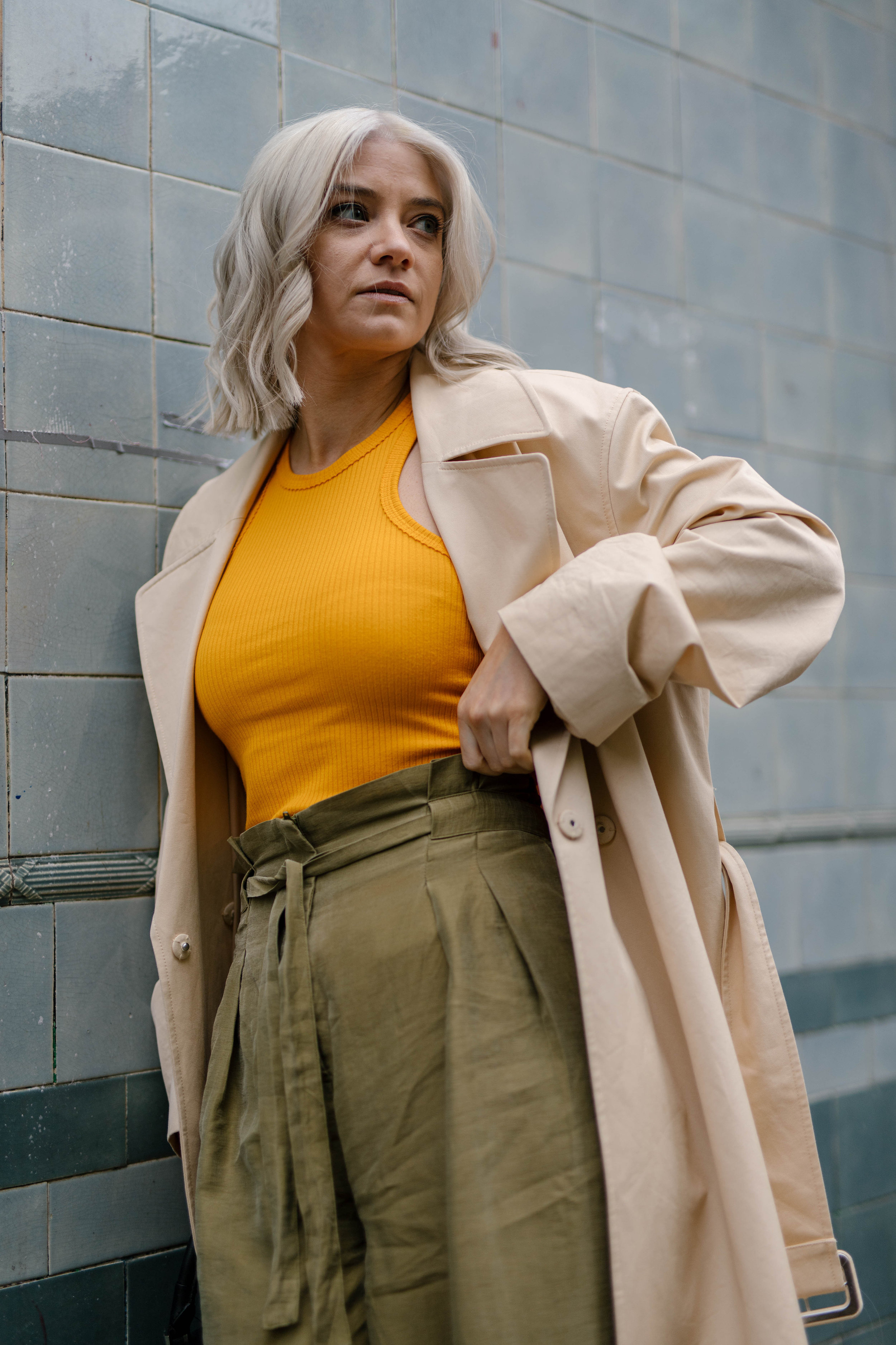 Freshly coloured platinum blonde bob, wearing a tank top and wide leg trousers and a trench coat, northern magpie, joey taylor 1