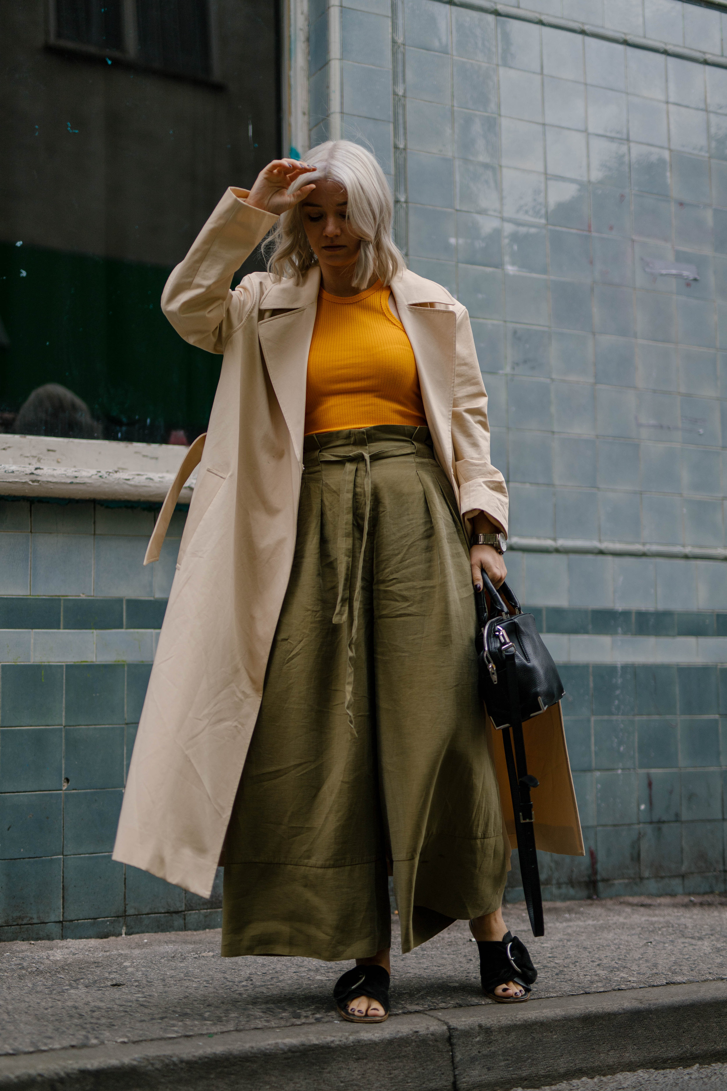 Freshly coloured platinum blonde bob, wearing a tank top and wide leg trousers and a trench coat, northern magpie, joey taylor 2