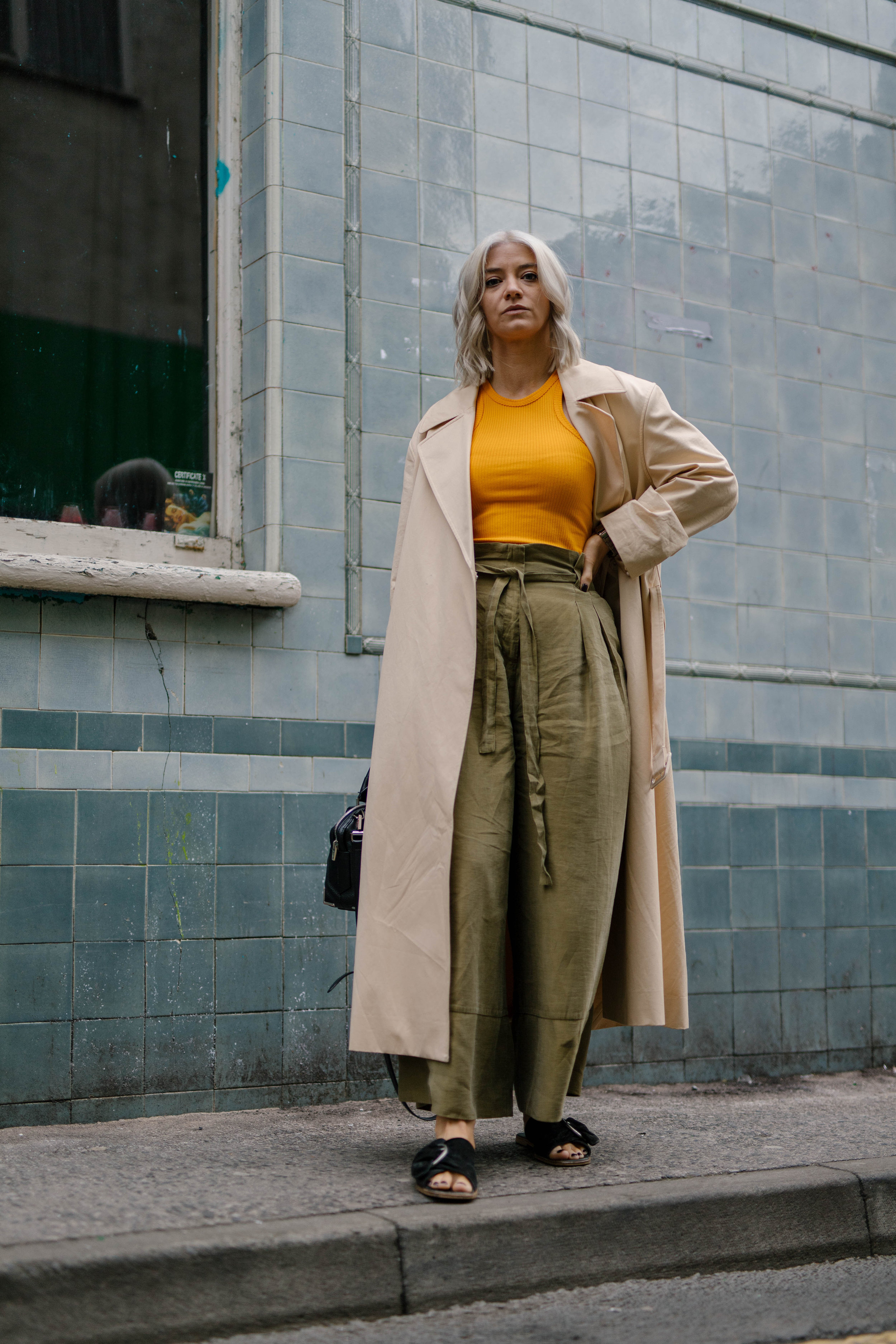Freshly coloured platinum blonde bob, wearing a tank top and wide leg trousers and a trench coat, northern magpie, joey taylor 3