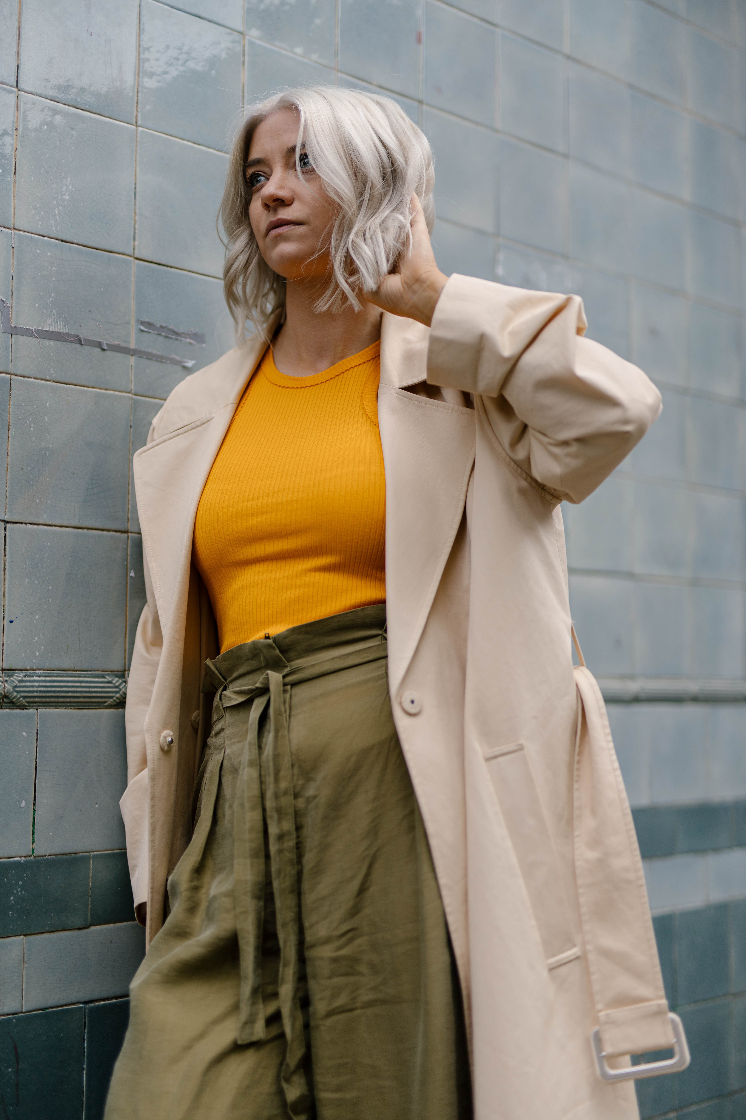 Freshly coloured platinum blonde bob, wearing a tank top and wide leg trousers and a trench coat, northern magpie, joey taylor 4