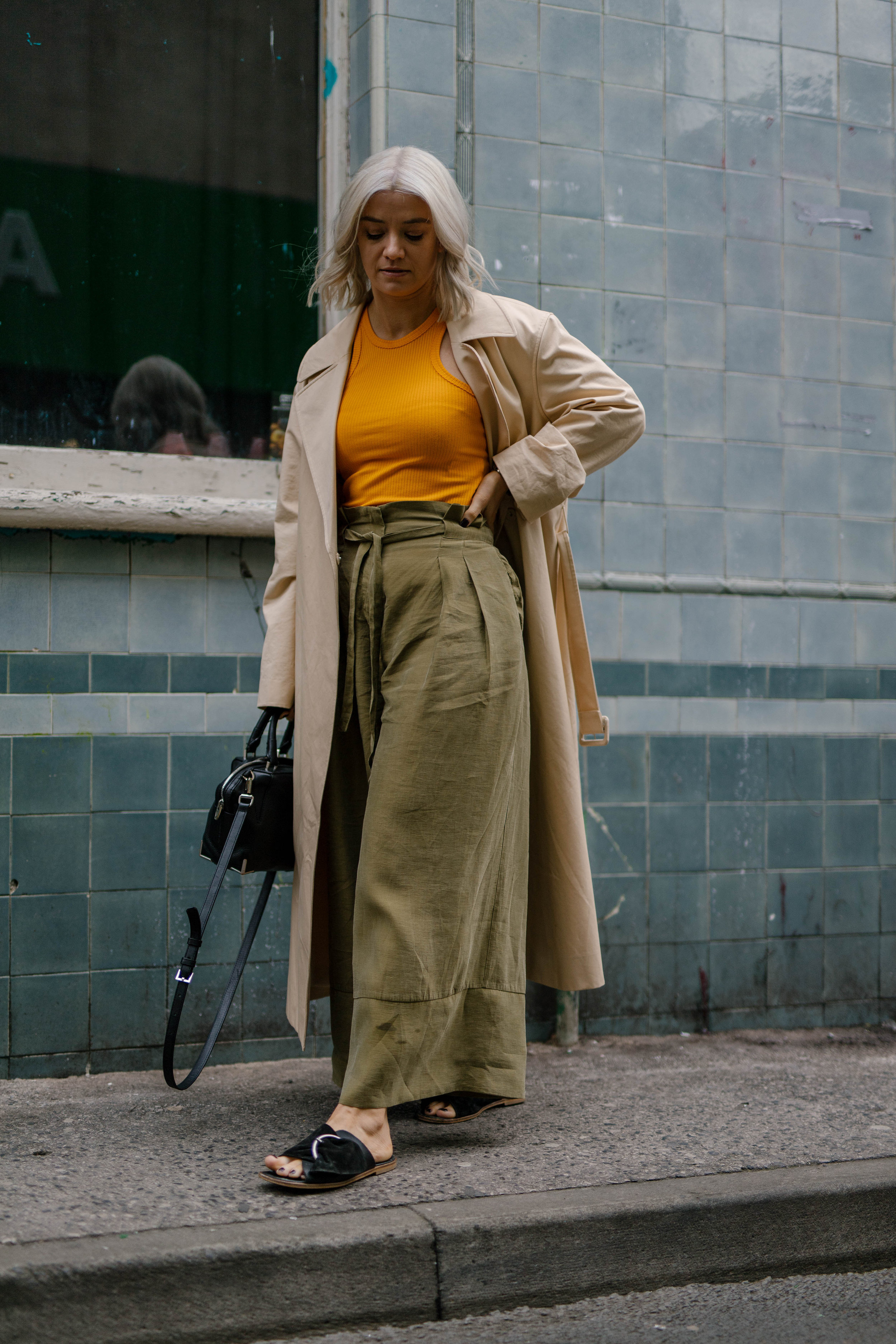 Freshly coloured platinum blonde bob, wearing a tank top and wide leg trousers and a trench coat, northern magpie, joey taylor 5