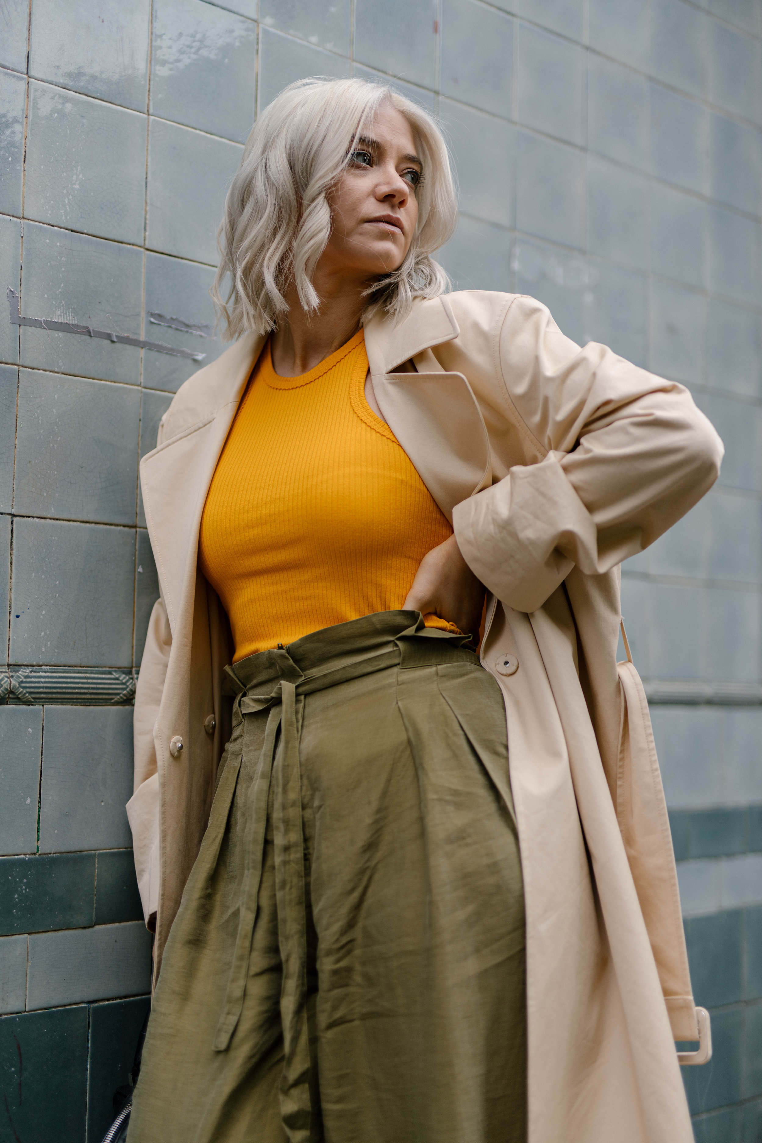 Freshly coloured platinum blonde bob, wearing a tank top and wide leg trousers and a trench coat, northern magpie, joey taylor 6