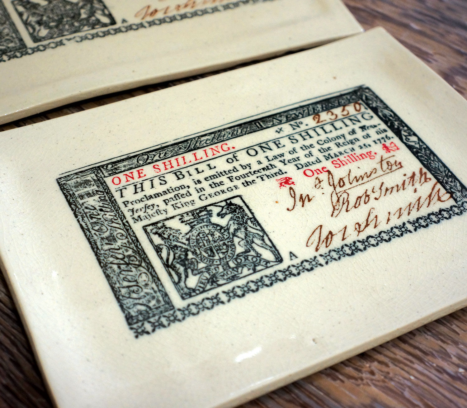 """NEW JERSEY COLONIAL CURRENCY   In 1664, 350 years ago this year, the Dutch surrendered New Netherland to the British and the colony of New Jersey was born . This imprint was created from original 1776 New Jersey colonial currency, one- and three-shilling notes (property of the artist), printed in New Jersey, and in use in New Jersey on the eve of the American Revolution.  Look for the royal colonial seal, flanked by a lion and a unicorn, as well as Benjamin Franklin's famous """"Join or Die"""" woodcut, on ceramic tiles, plates, ornaments, and pendants."""