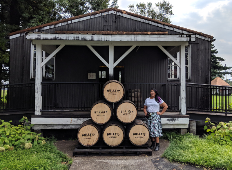 In front of the barrel pyramid at Bulleit, wearing an  Alice Riot  skirt.