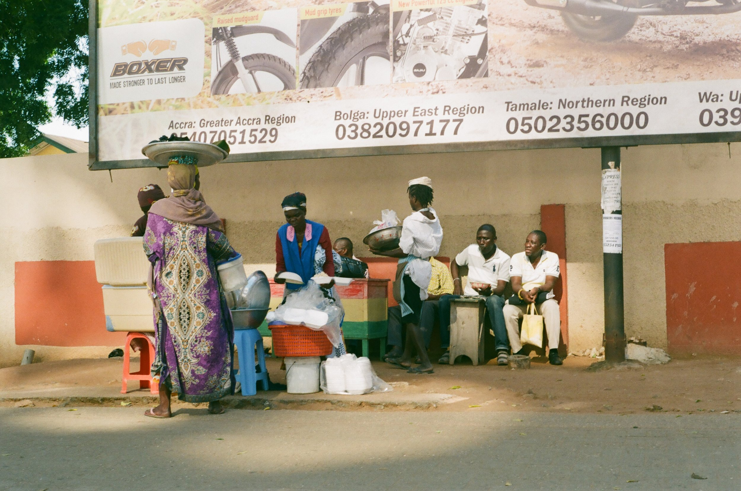 Taken from inside the taxi, this image shows a typical street scene in Accra of food being served and eaten roadside.