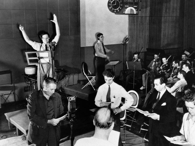Canlı radyo programından bir kare. Welles kendini rolüne kaptırmış, yardımcı oyuncular repliklerine bakıyorlar, orkestra da bahşiş bekliyor.