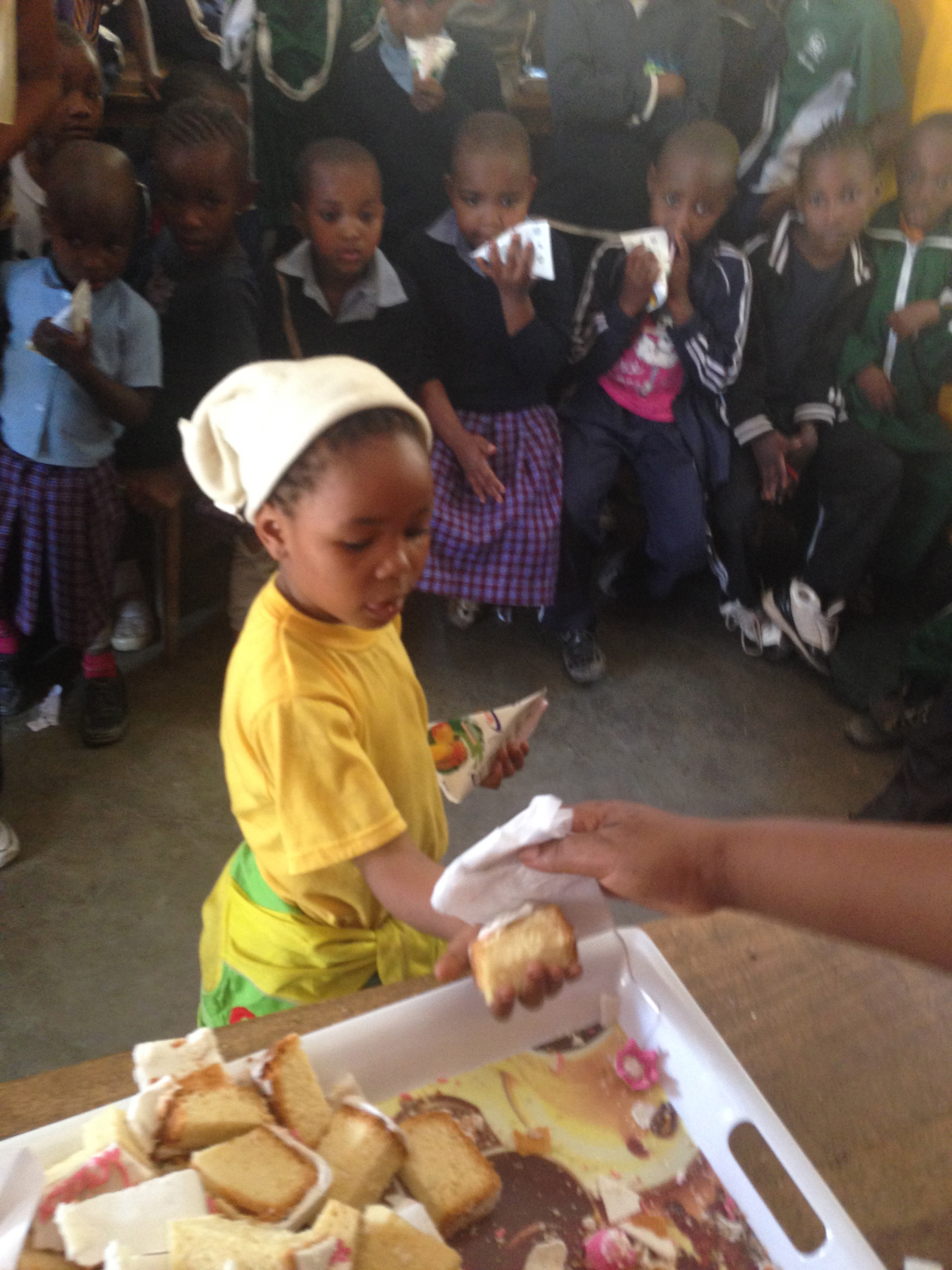 Here is Alice handing out tasty pieces of cake to each of the kids!