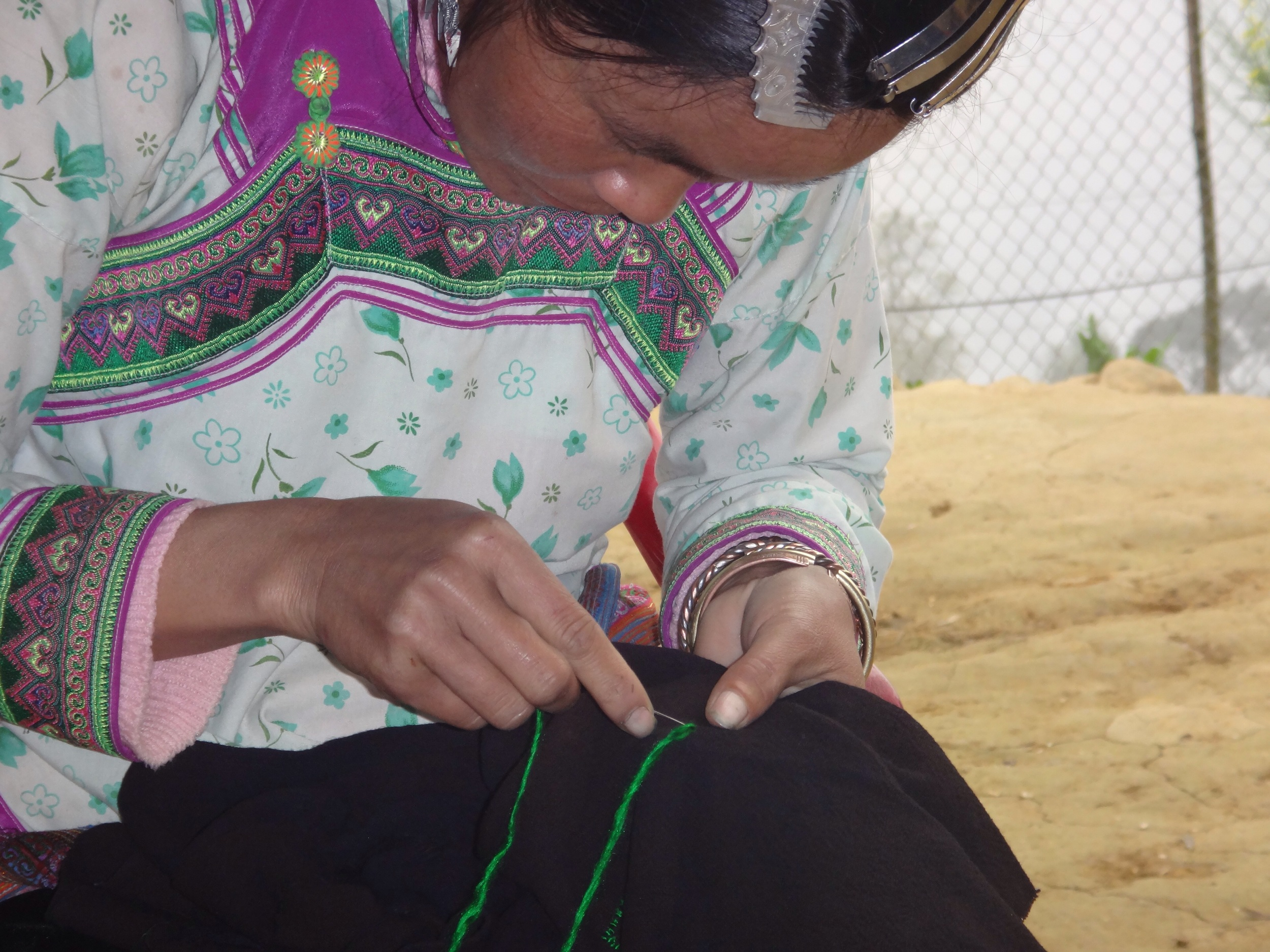 Ker, doing traditional Hmong embroidery for a belt, would take about 1.5 years to complete.