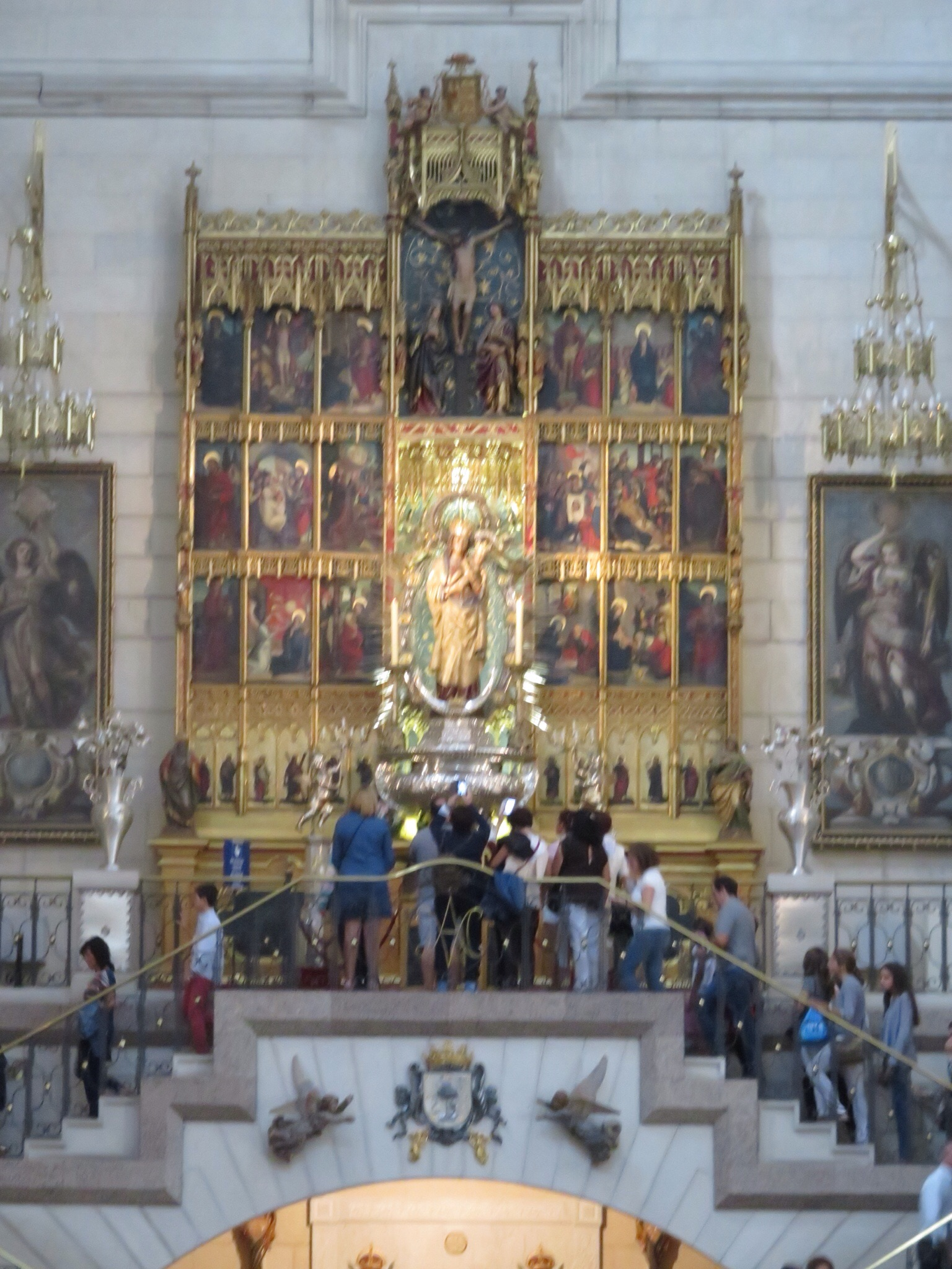 15th century altarpiece with tomb of Queen Maria de la Mercedes below - congregation receiving Sunday blessings.