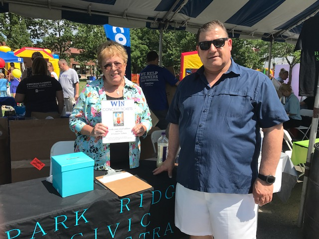 """Pictured: Phyllis Doyle and Mike Olson manning the table at """"Canopies on Courtland"""" at the Taste of Park Ridge Saturday, July 15, 2017."""