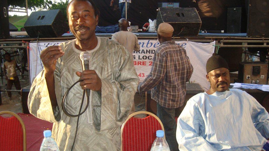 Lamine donne son discours sur la santé de la communauté lors de la conférence . Sur sa gauche se trouve le guide religieux et chercheur en médecine traditionnelle.
