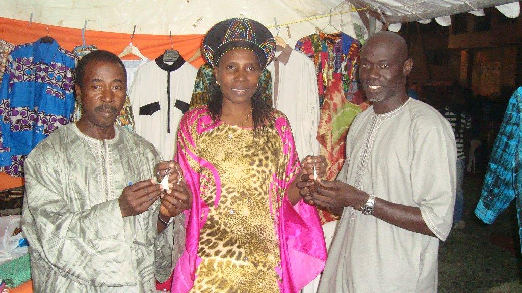 Lamine et Idrissa reçoivent des cadeaux d'une participante à la foire.