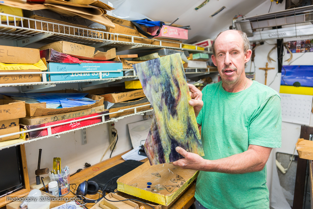 Denver Stained Glass Artist in Green Shirt holding a piece of raw stained glass