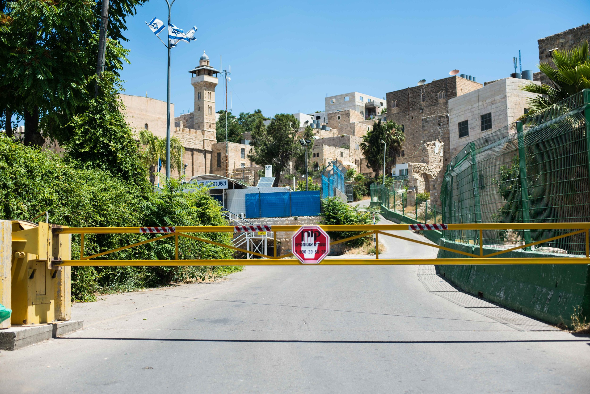 "Generally, this gate is not closed and the road remains open.  When it is open, Hebron residents are supposed to ""know"" the paved left side is for Jewish Israelis while the dirt path on the other side of the green mesh fence to the right is for Palestinians.  Hebron, West Bank, Palestine."